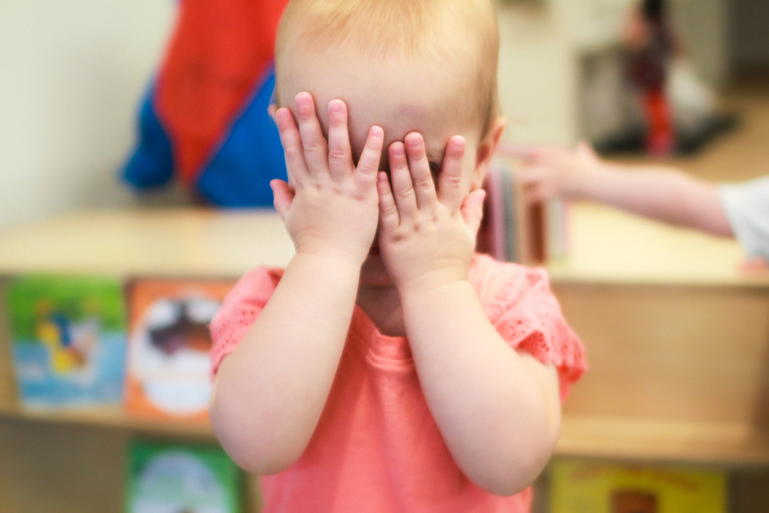 Toddler playing peak-a-boo