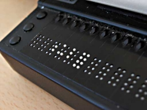 Image shows the first few cells of a braille display. To the left of the display panel are three circular buttons places vertically meant for navigation. Along the top are the routing keys.