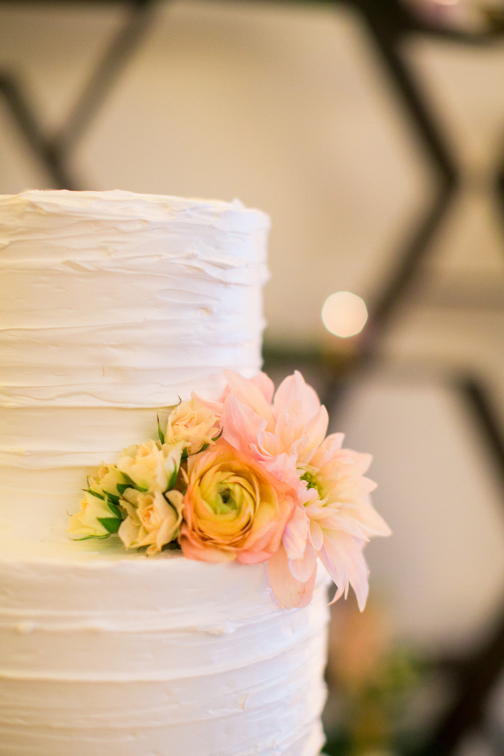 e18c4-elegant-country-charm-ranch-wedding-stunning-tiered-cake-with-soft-spray-of-flowers.jpg
