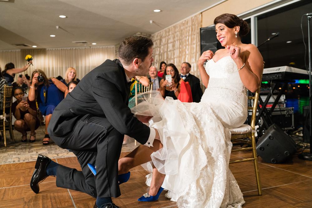 7d681-lively-navy-yellow-harbor-wedding-groom-searching-for-garter.jpg