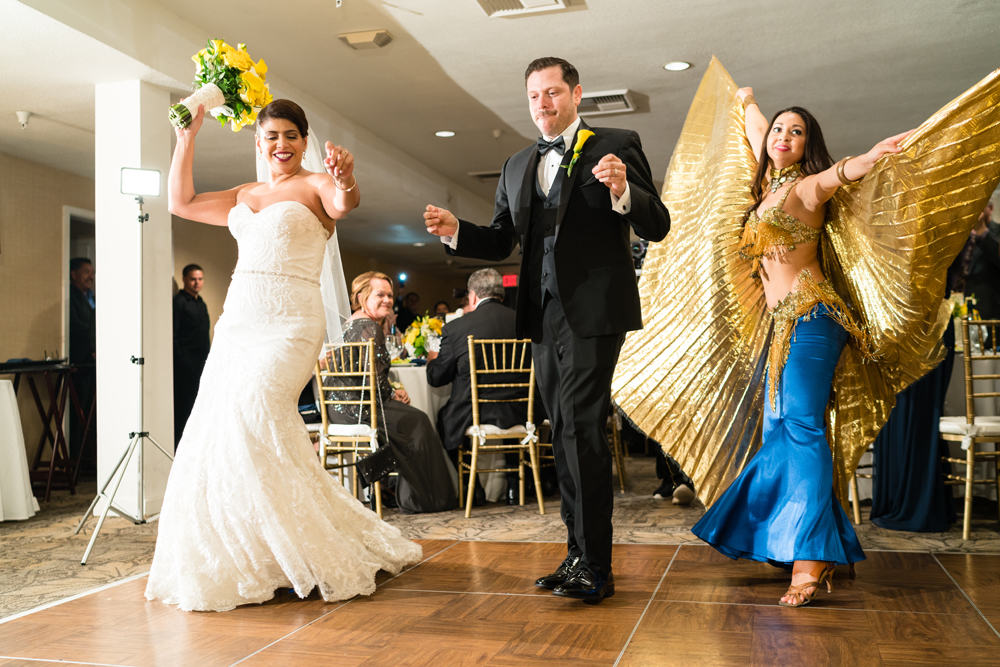 b91d5-lively-navy-yellow-harbor-wedding-bride-and-groom-entering-reception-with-belly-dancers.jpg