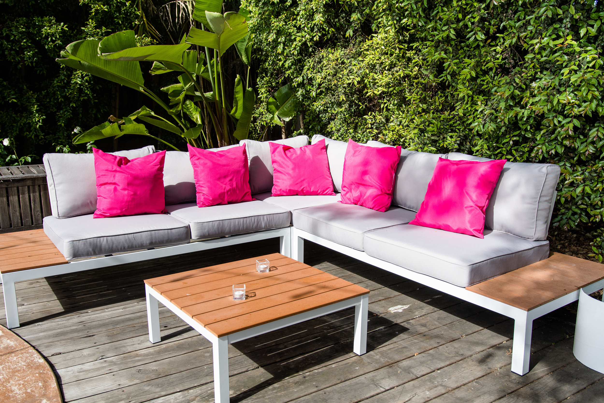Vibrant Fiesta Backyard Wedding Reception cozy seating area with hot pink pillows.jpg