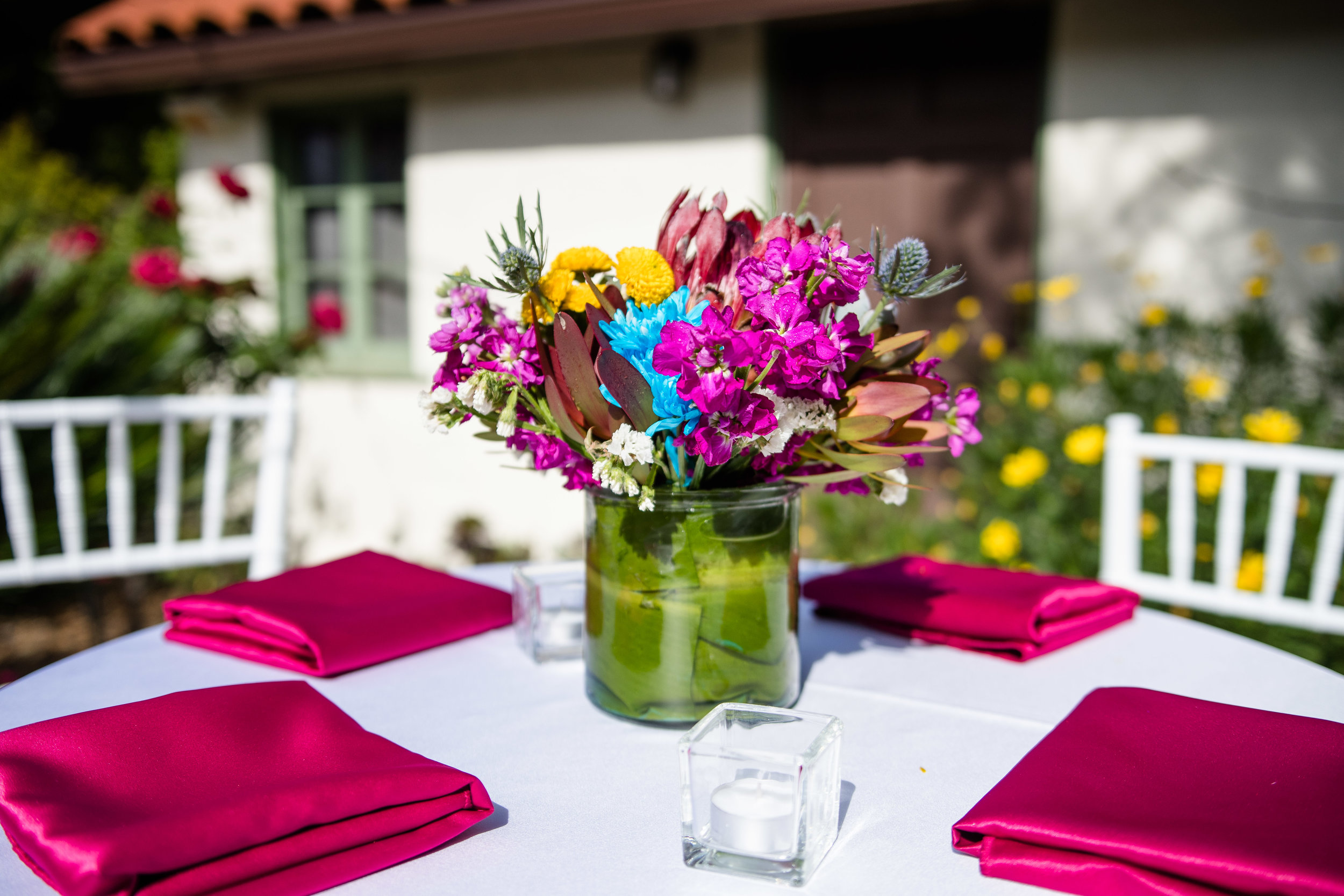 Vibrant Fiesta Backyard Wedding Reception spring florals adorned each table with hot pink linens.jpg