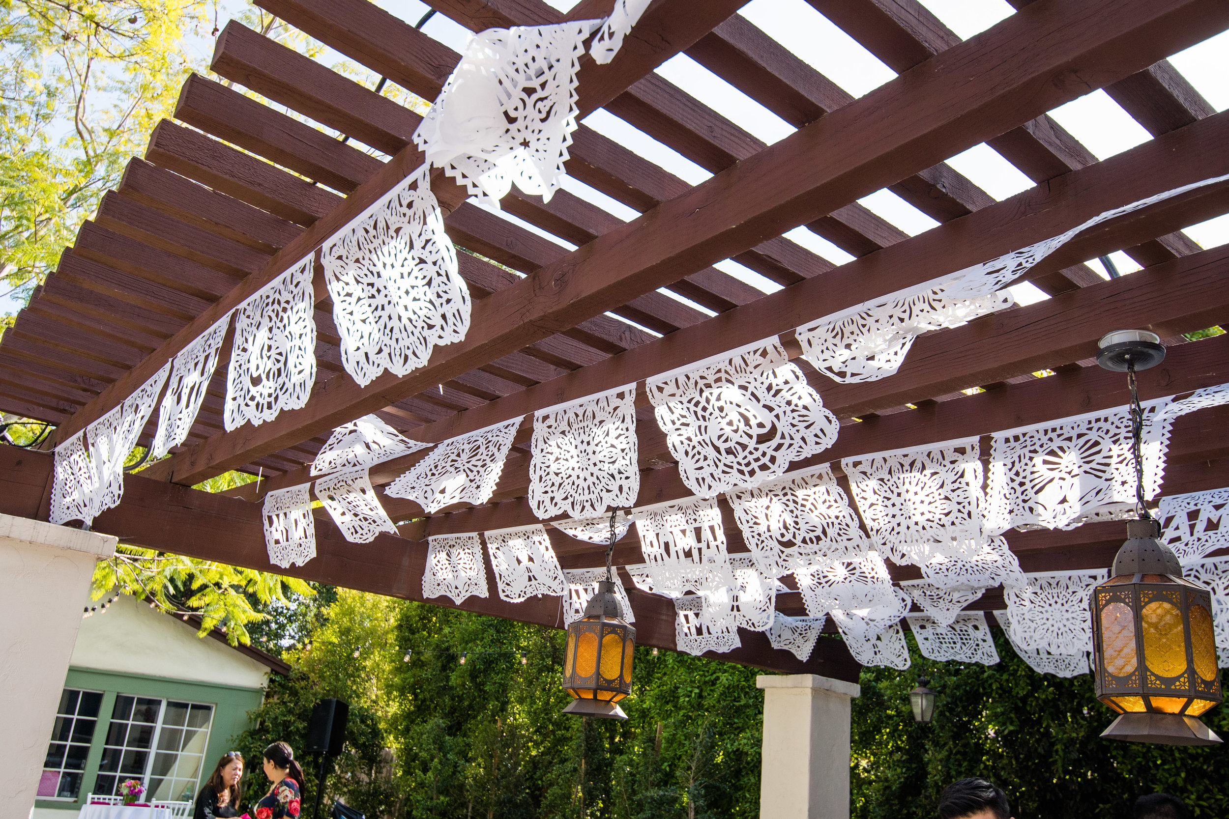 Vibrant Fiesta Backyard Wedding Reception mexican picado banners hanging from the pergola.jpg