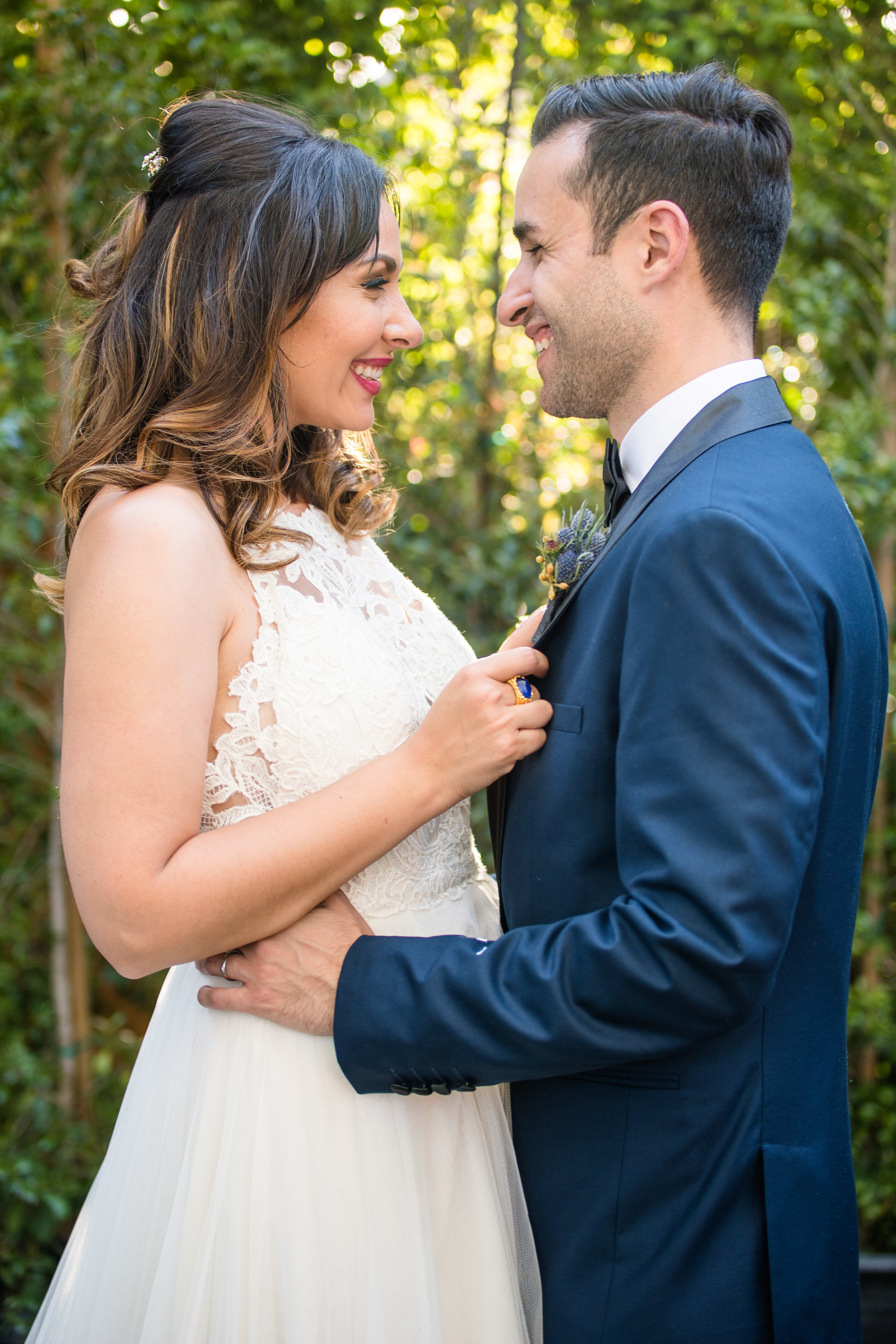 Vibrant Fiesta Backyard Wedding Reception bride and groom pose in front of lush trees.jpg