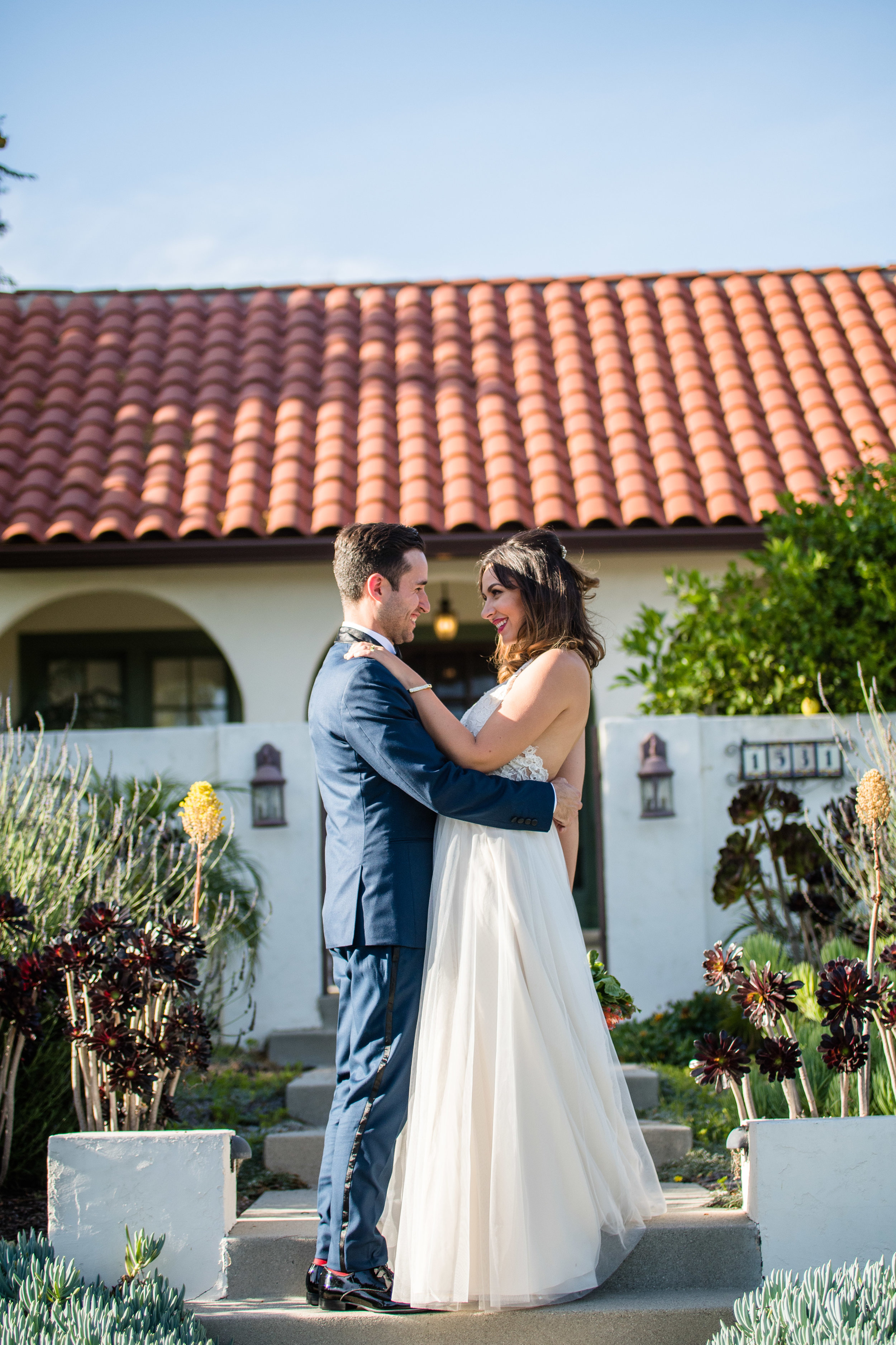 Vibrant Fiesta Backyard Wedding Reception bride and groom pose in front of reception home.jpg