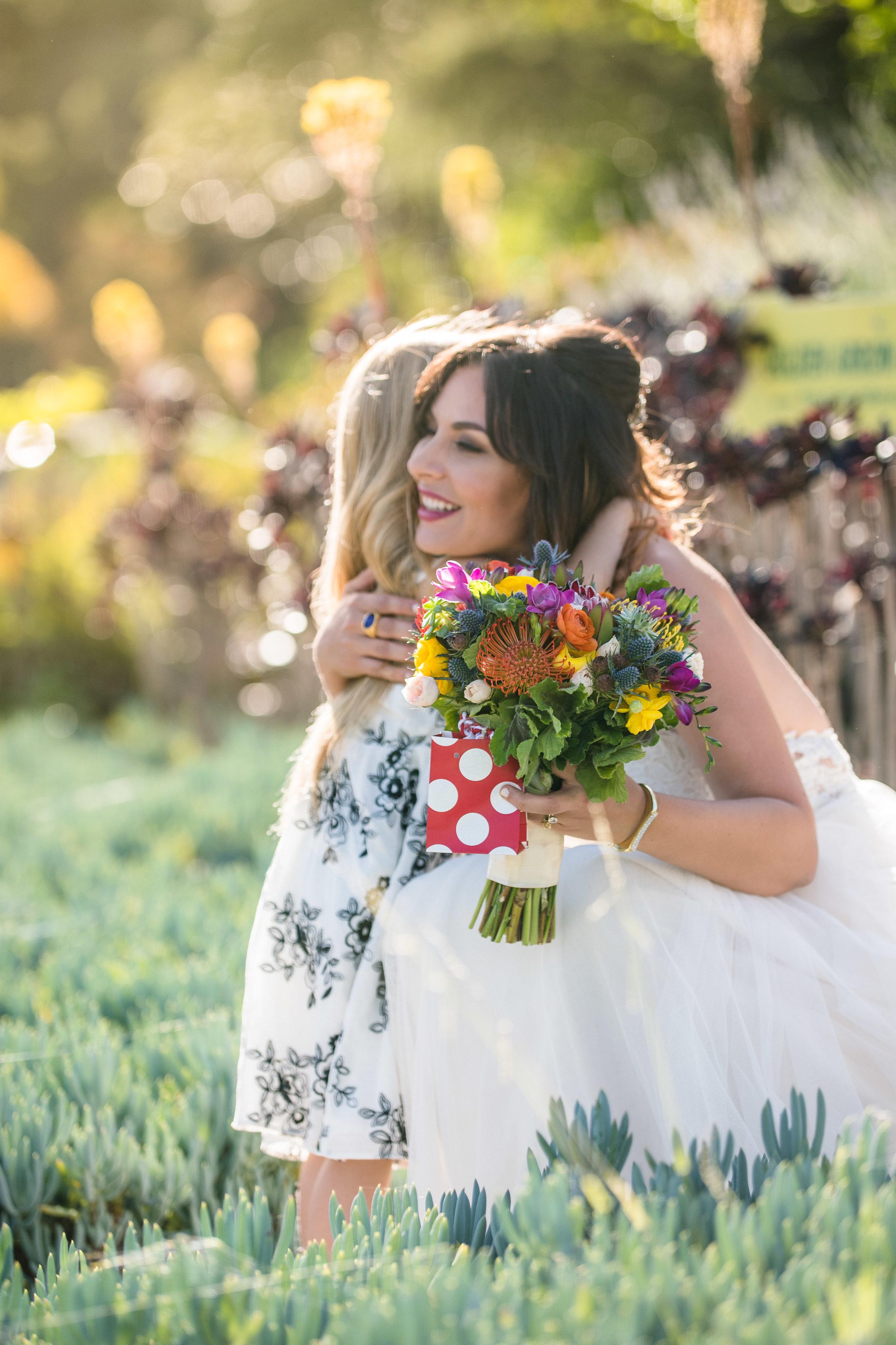 Vibrant Fiesta Backyard Wedding Reception bride hugging little guest.jpg