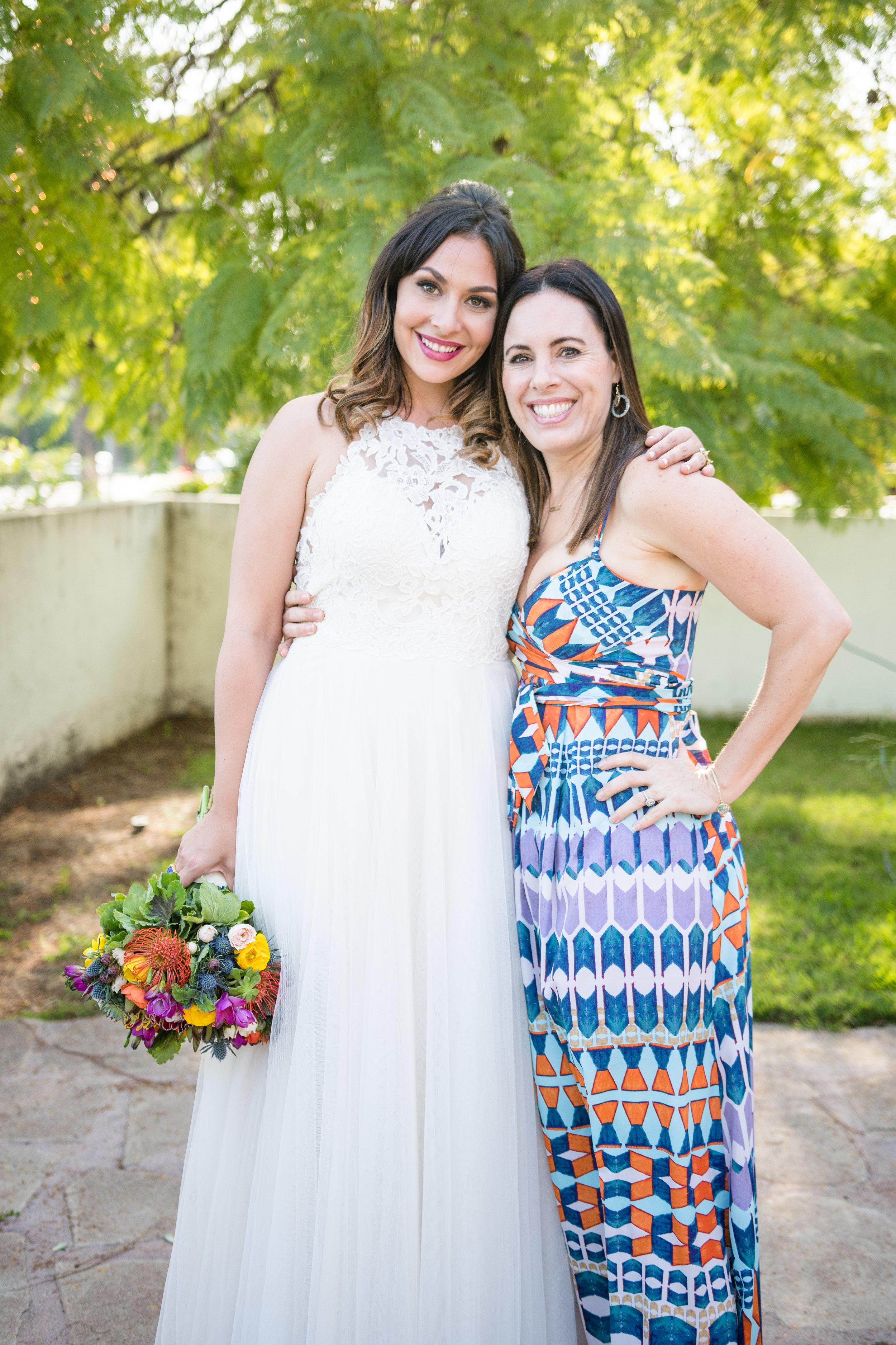 Vibrant Fiesta Backyard Wedding Reception bride posing with wedding guest.jpg
