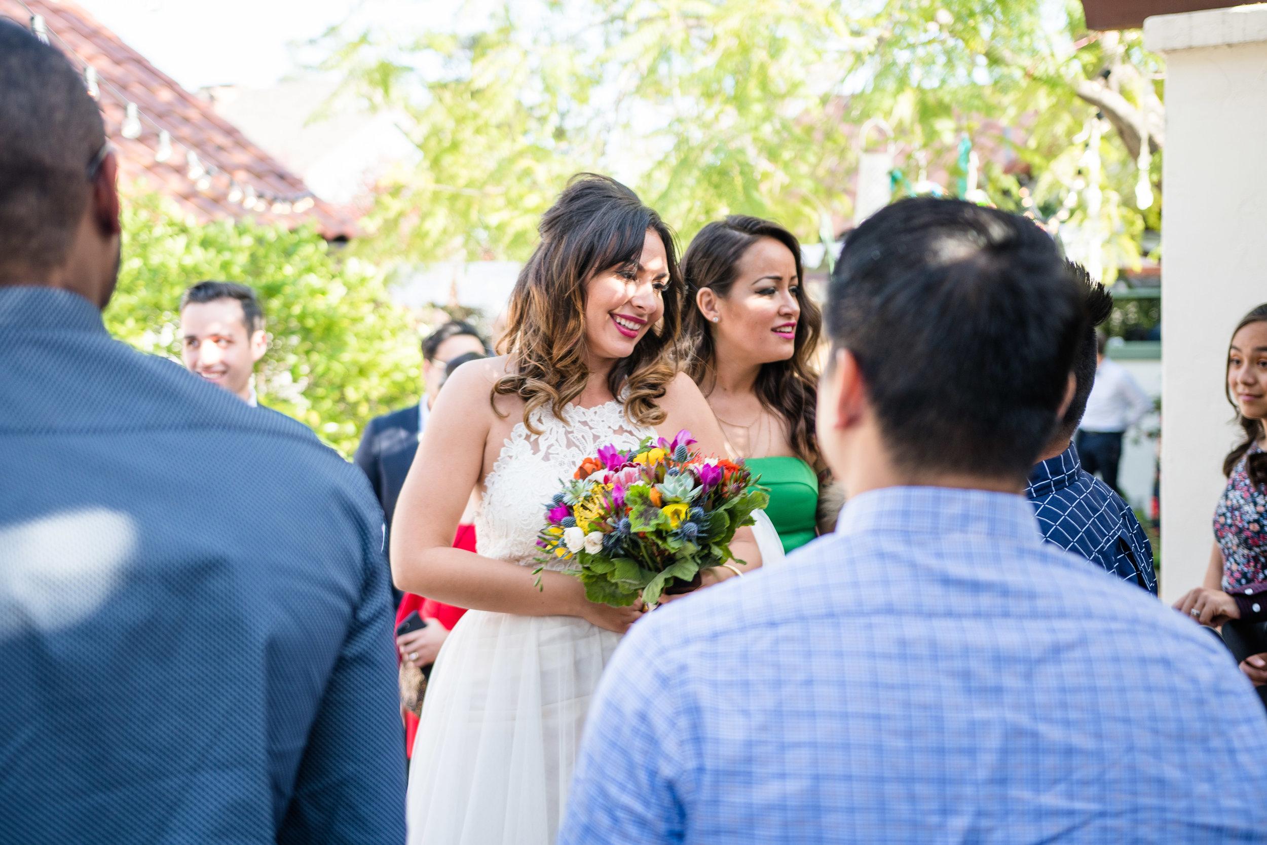 Vibrant Fiesta Backyard Wedding Reception bride carrying bouquet greeting guests.jpg
