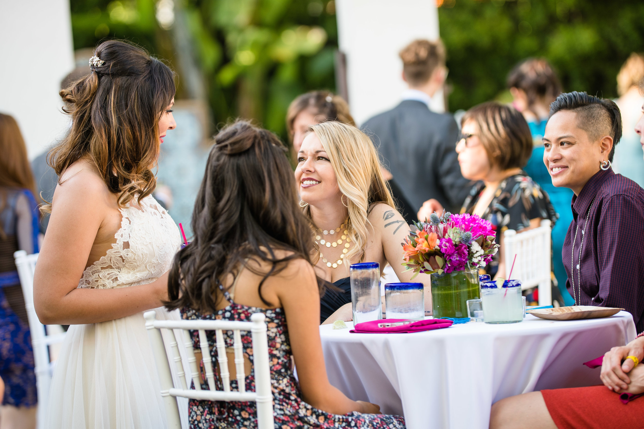 Vibrant Fiesta Backyard Wedding Reception bride making the rounds to greet guests.jpg
