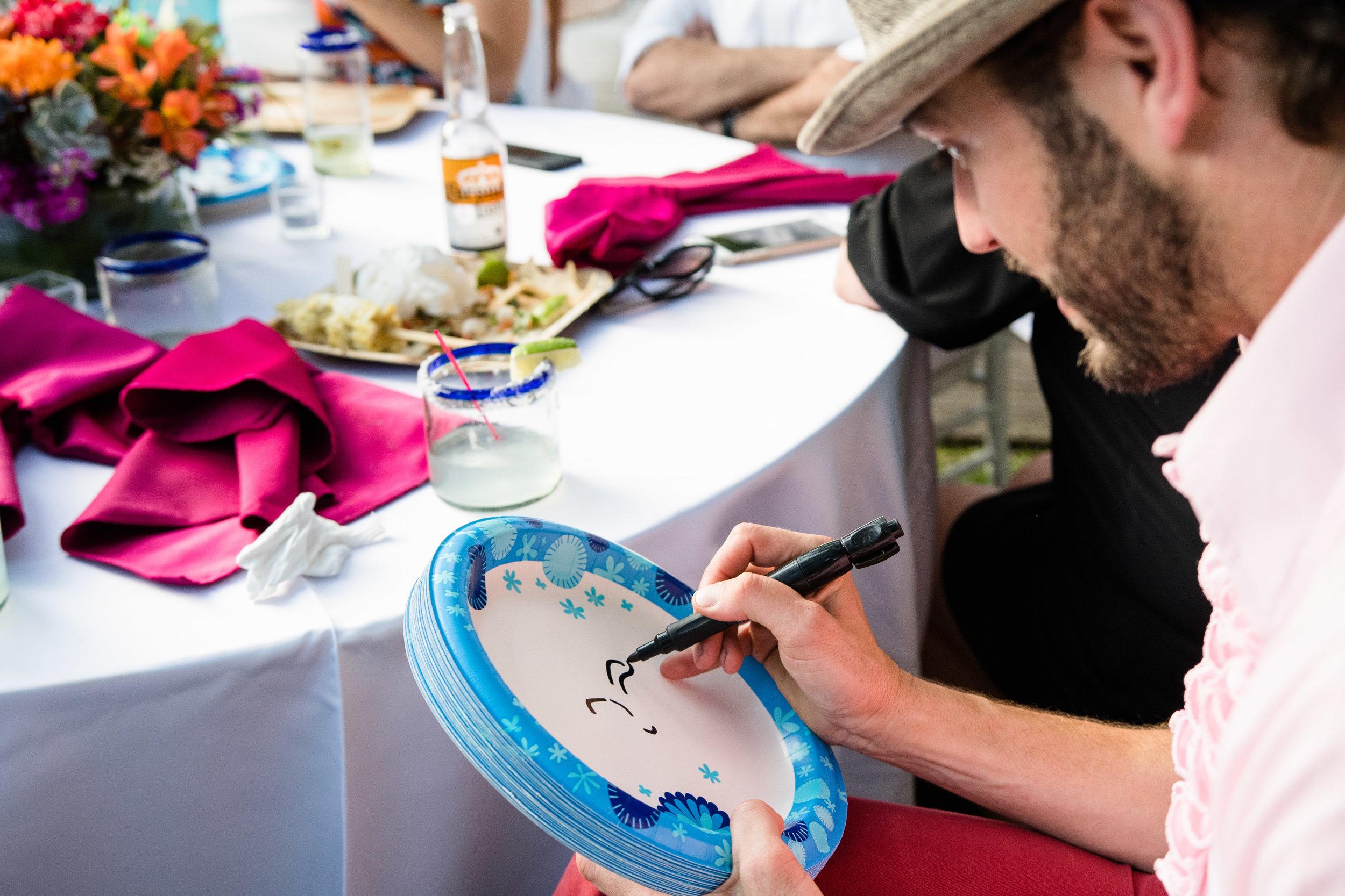 Vibrant Fiesta Backyard Wedding Reception guest decorates paper plates.jpg
