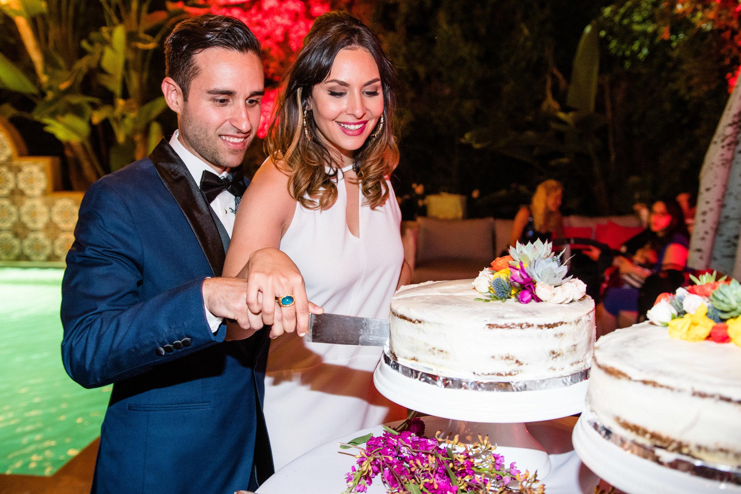 Vibrant Fiesta Backyard Wedding Reception bride and groom cutting cake.jpg