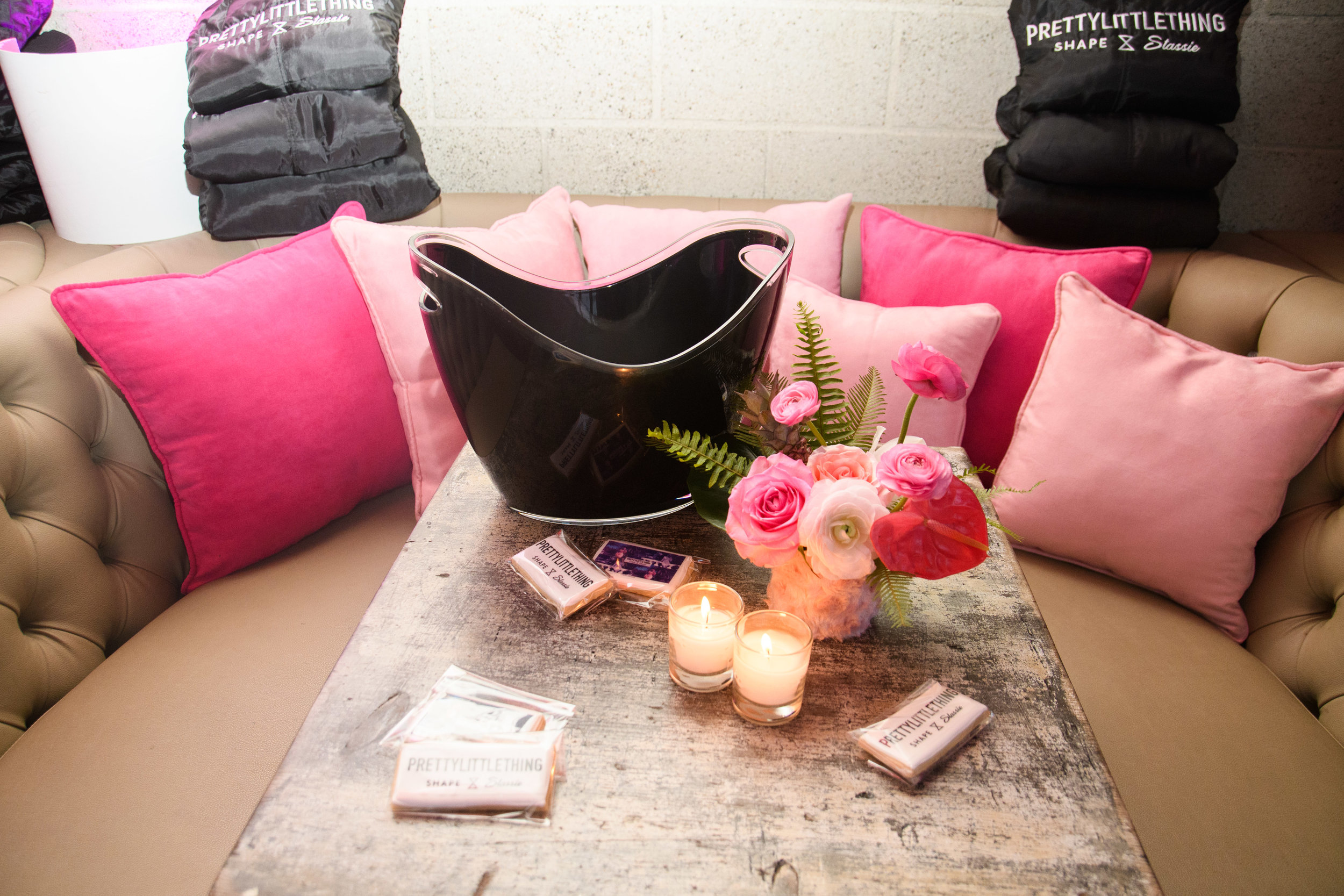 PrettyLittleThing New PLT Shape Collection with Stassie Celebrity Launch Party black laquer ice bucket on the table and pretty pink pillows on the bench.jpg