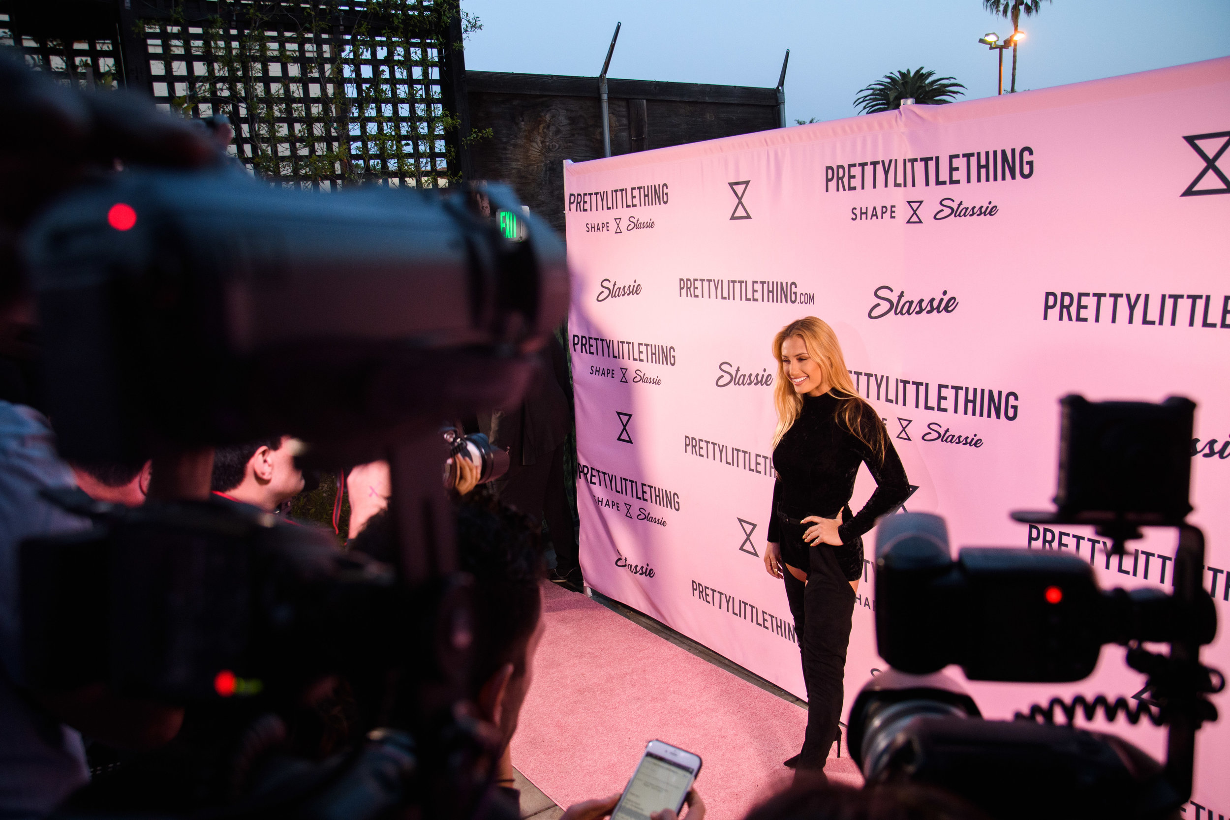 PrettyLittleThing New PLT Shape Collection with Stassie Celebrity Launch Party sneak peek of what step and repeat looks like with photographers with Montana Tucker.jpg
