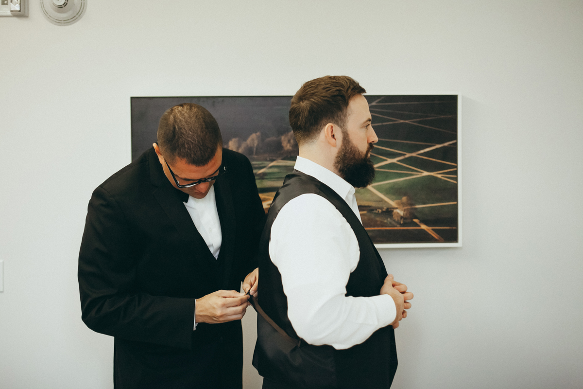 Breathtaking Contemporary Jewel Toned Fall Posh Wedding groomsman helping groom.jpg