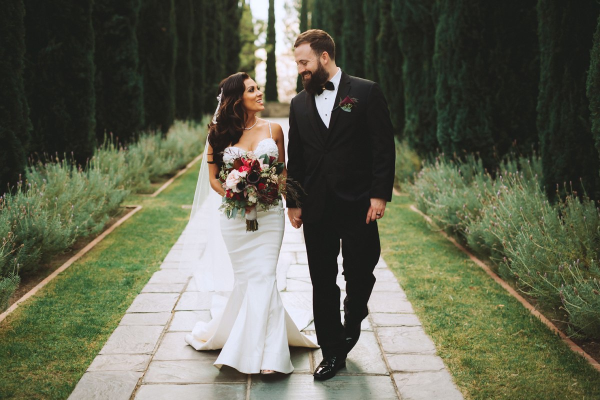 Breathtaking Contemporary Jewel Toned Fall Posh Wedding bride and groom walk the gardens.jpg