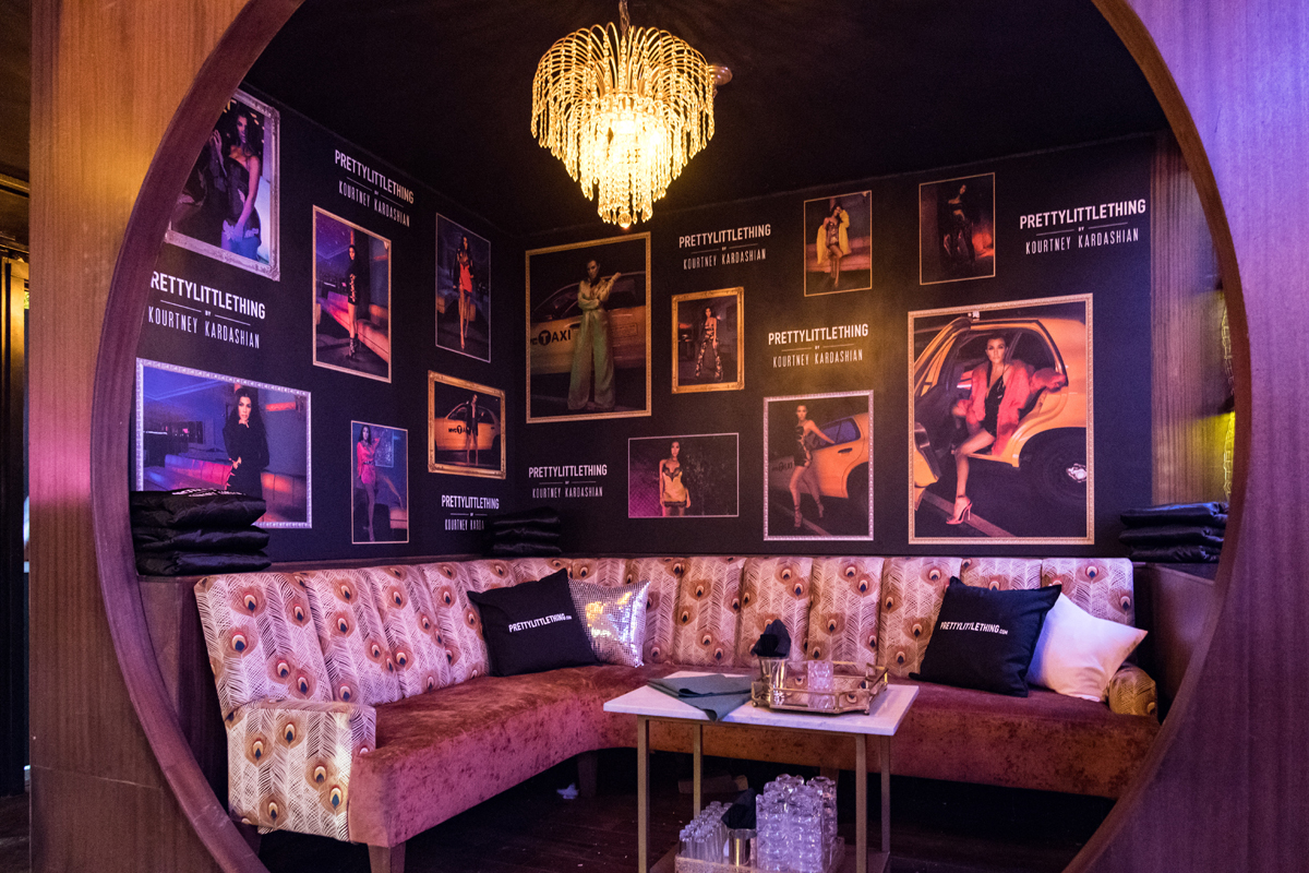 PrettyLittleThing PLT X Kourtney Kardashian Collection Celebrity Launch Party VIP area with posters of the collection.jpg