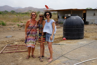Standing in front of the water tank. All of the water necessary for construction must be trucked in and stored. The completed resource center will feature a community well and drinking fountain.