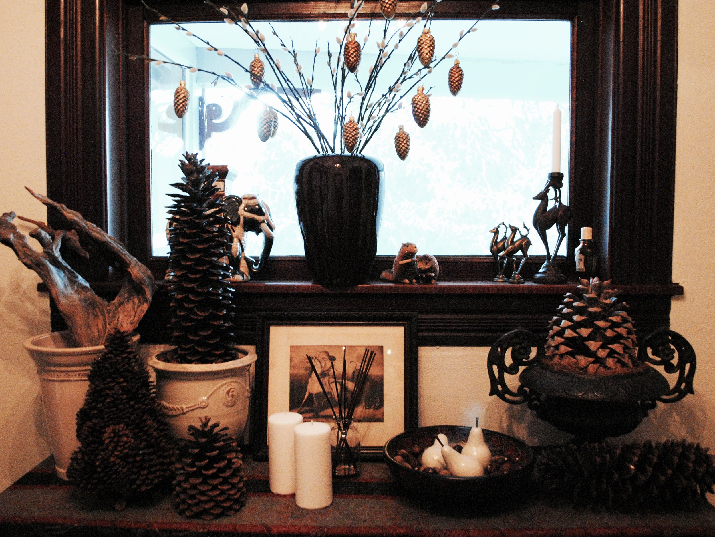 In the vestibule, pine cones, wooden pears,and a bowl of chestnuts on the old Italian ironwood console.