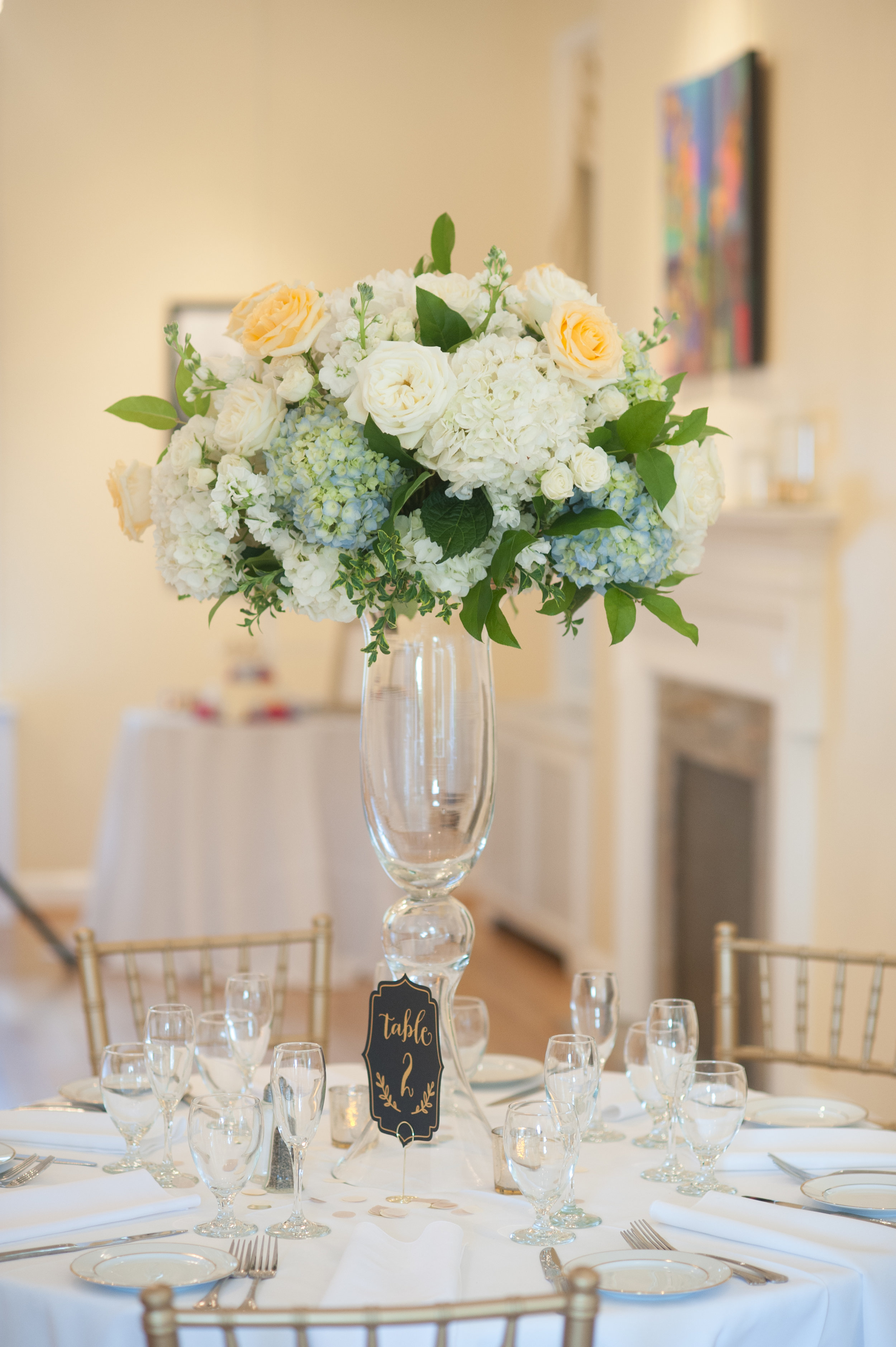 Tall centerpiece with muted colors and greenery at  Kentlands Mansion  in Gaithersburg, MD. Roman Grinev Photography