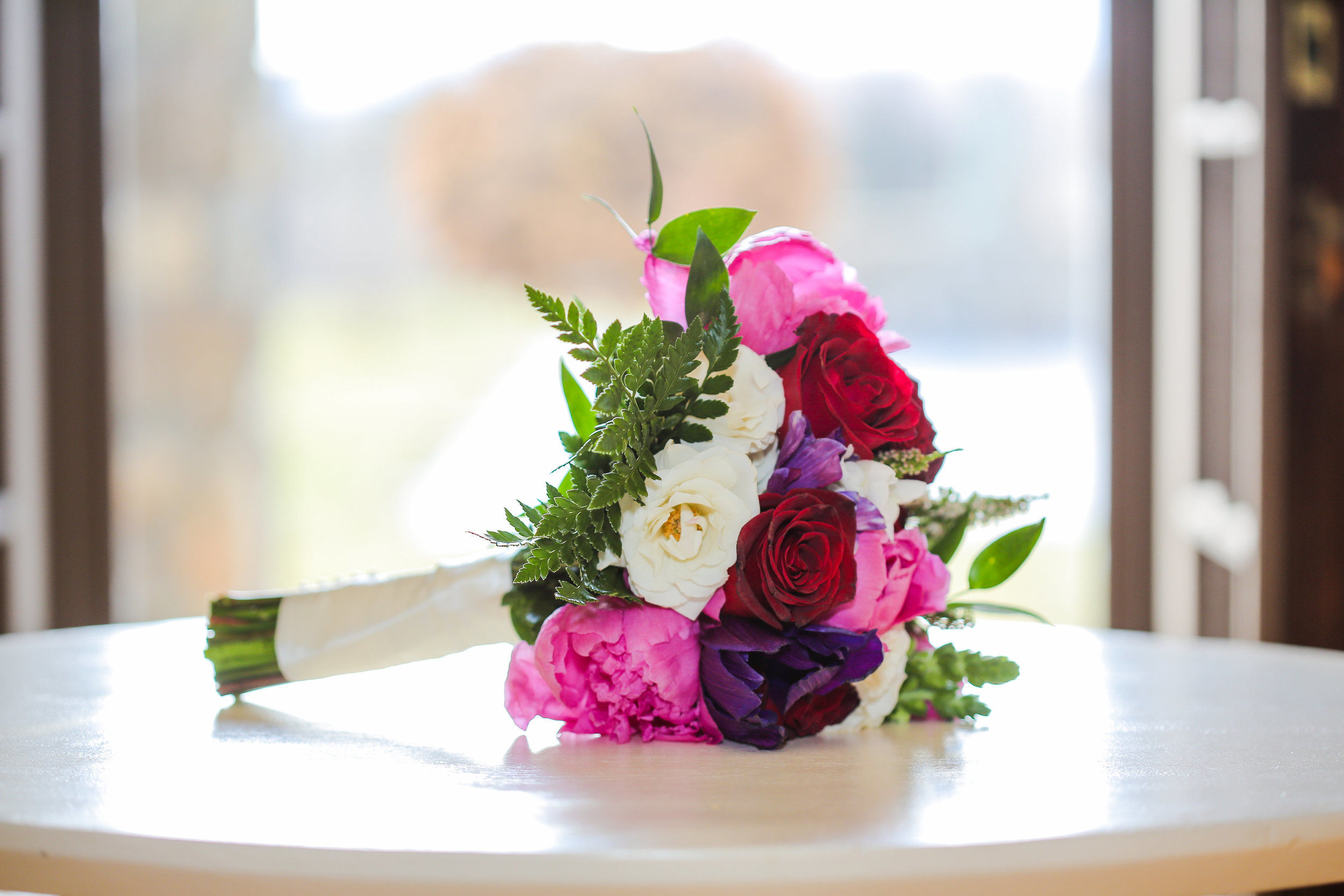 Bridal bouquet with deep purple anemone, pink peonies and red roses. This is perfect for a bride that loves bright colors. Raiza Vega Photography