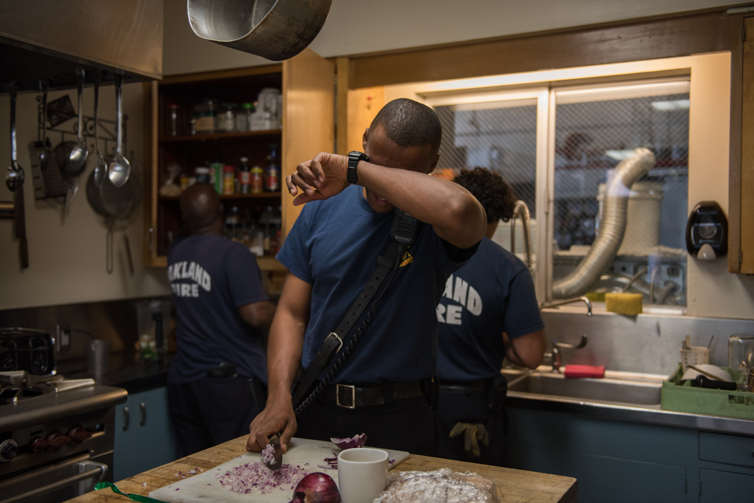 Firefighter Paul Mason Jr wipes his eyes as he chops onions for the crew's dinner at Oakland's Station 23 on Monday, June 26, 2017. | Rosa Furneaux for the East Bay Express