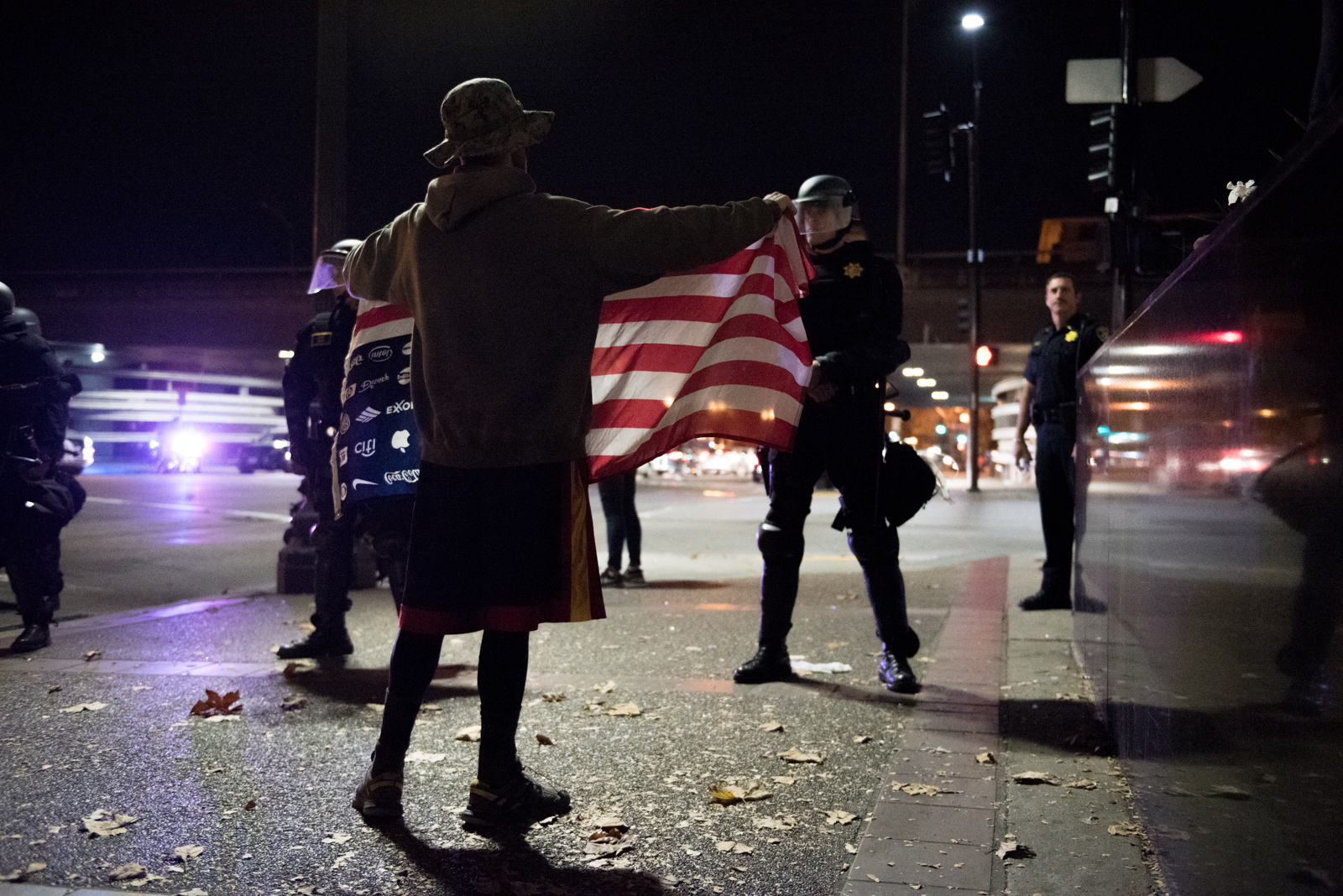 A protester stands in front of a police line on Broadway, near Interstate 880, in Oakland on Friday, October 11, 2016. | Rosa Furneaux/Oakland North