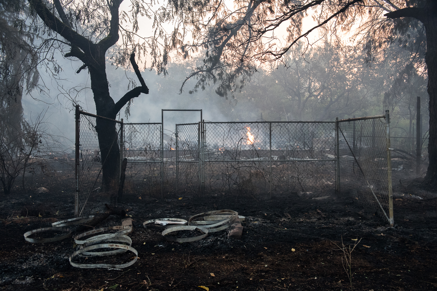 The remains of a burned house smoulder on the morning of Saturday, 14 October 2017, as the sun rises on Sonoma during the devastating North Bay wildfires.
