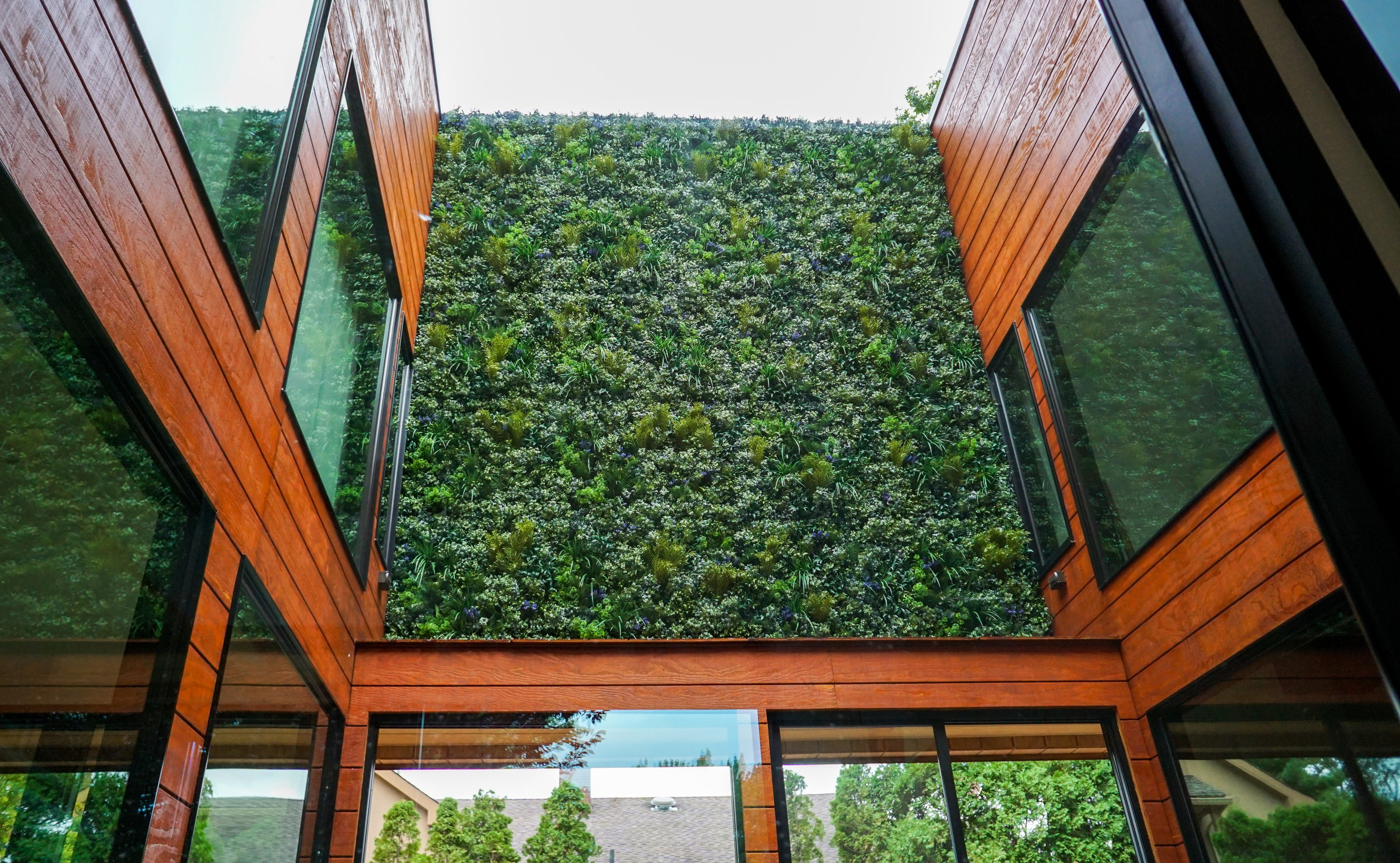 ALW Installation at a Home in NY  An artificial living wall in an indoor/outdoor atrium in Staten Island, NY. Artificial plants were the perfect solution for this project since they will stay vibrant year-round and be resistant to the elements.