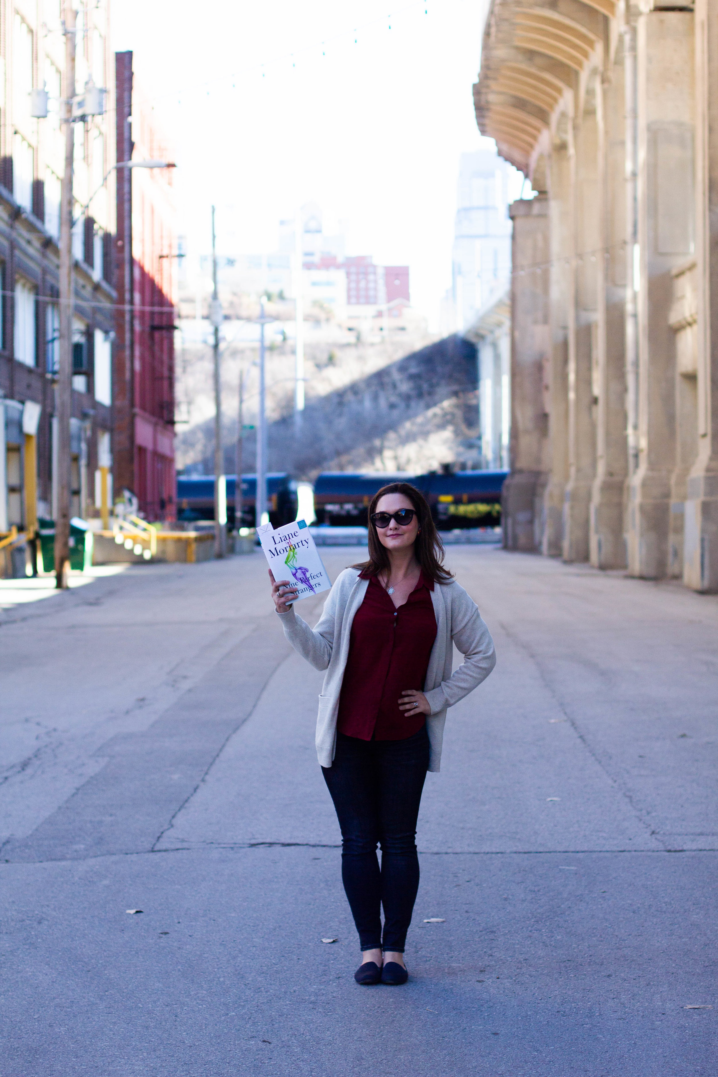 Reading Nine Perfect Strangers by Liane Moriarty in the Historic West Bottoms district of Kansas City, MO