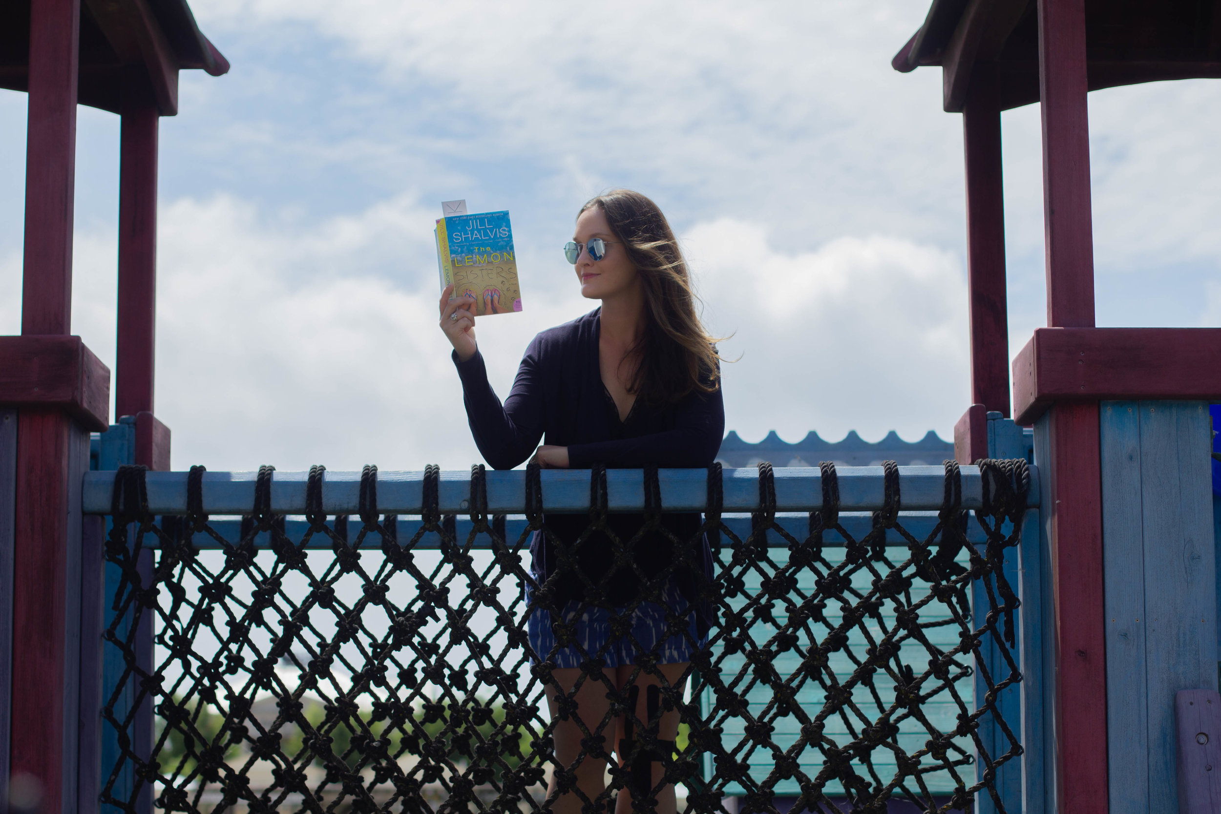 Reading The Lemon Sisters by Jill Shalvis at a playground in New Town at St. Charles, MO