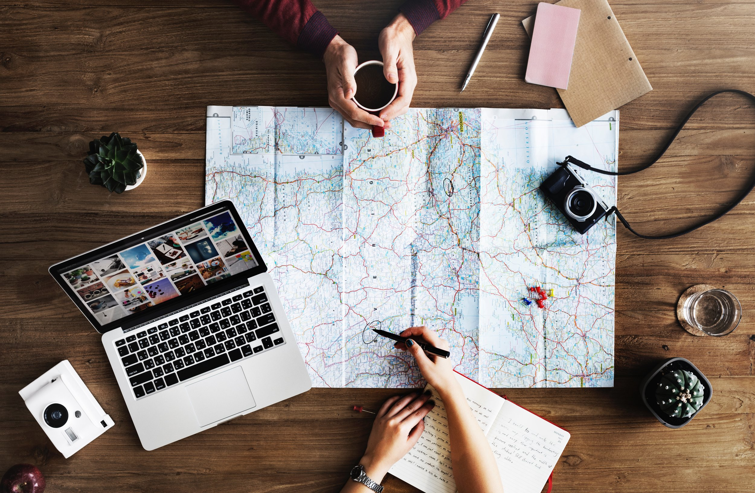Two travellers plan out their trip with a map, notebook, camera, laptop, and cup of coffee.