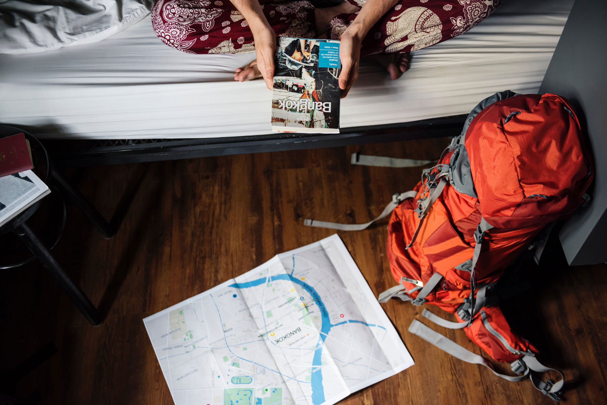 Someone on a cozy hostel bed reads a city guide and map next to their backpack.