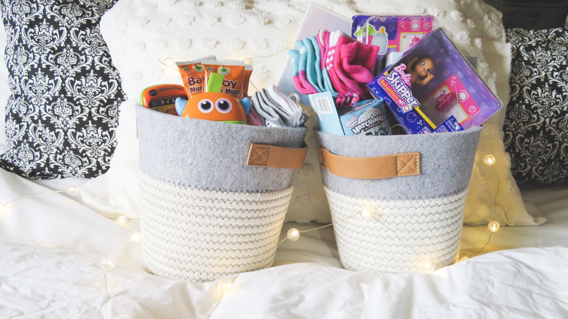 easter baskets for sisters, two easter baskets for a baby and a preschooler, two easter baskets with decorative baskets from target, new socks, fisher price monster toy, toy phone, snacks, no candy easter basket ideas, barbie dolls, new movie