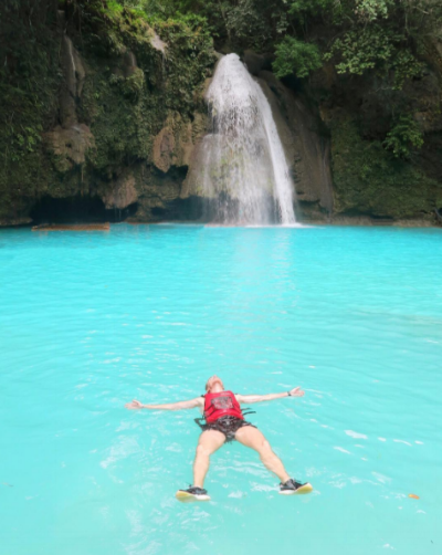 Floating in the bright blue waters of Kawasan Falls