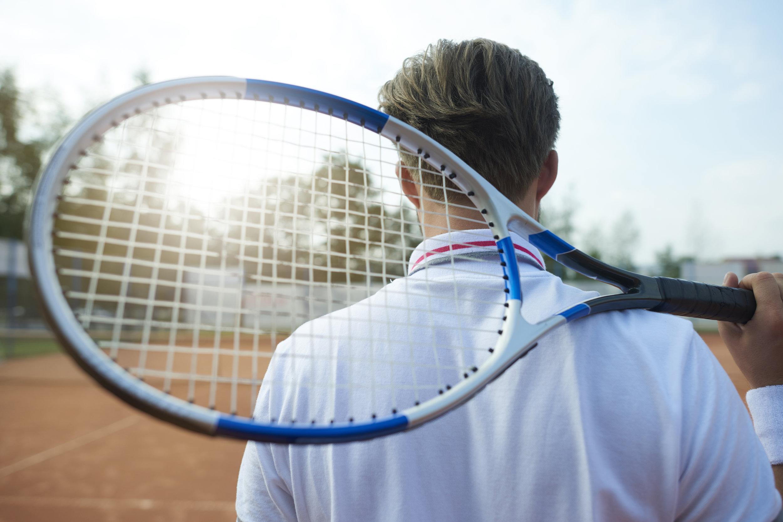 storyblocks-man-is-holding-a-tennis-racket_rPxmv-JF9M.jpg