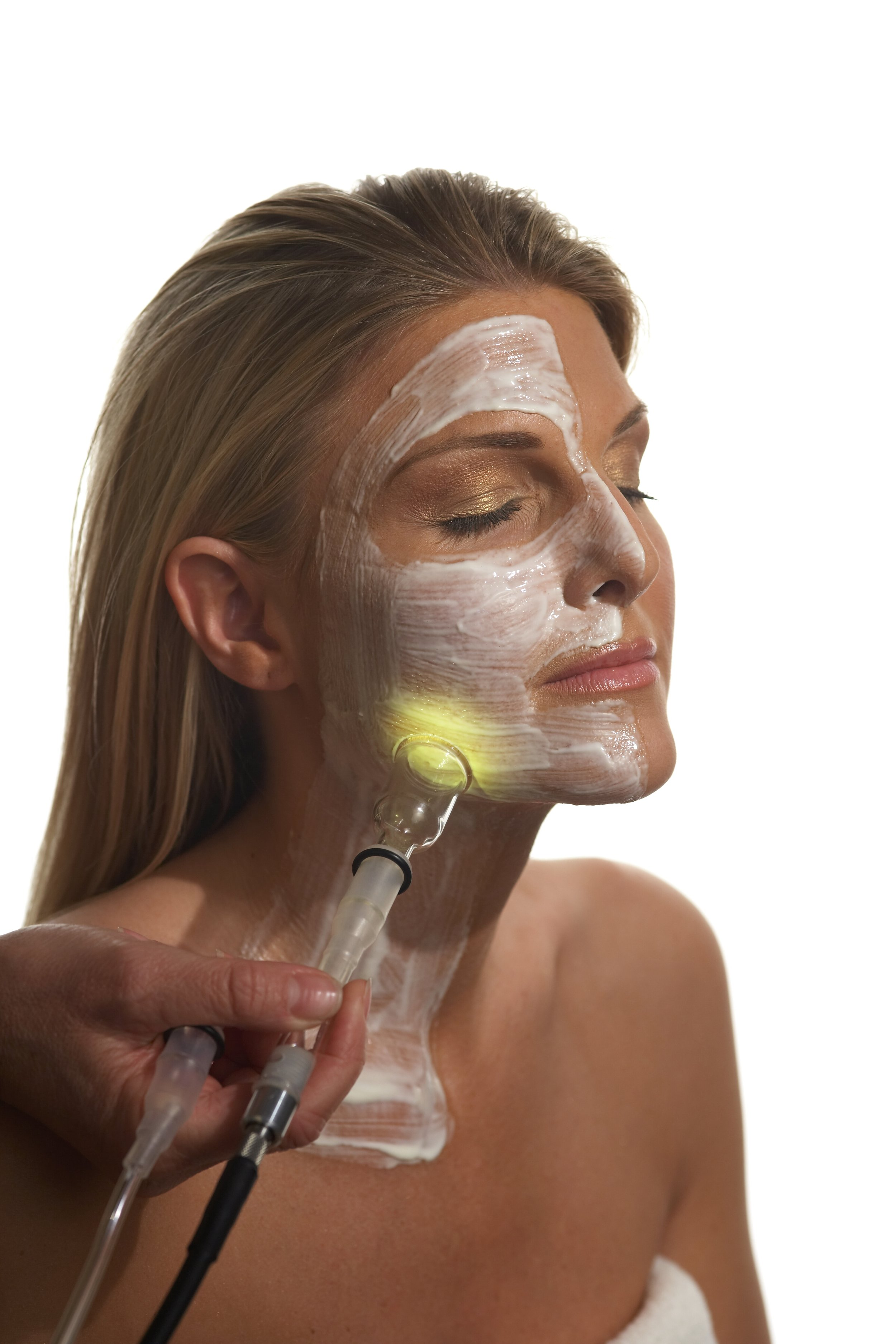 A woman receiving a PHYTO5 facial with quantum energetic skincare products and a lymphatic drainage enhanced with colored light therapy
