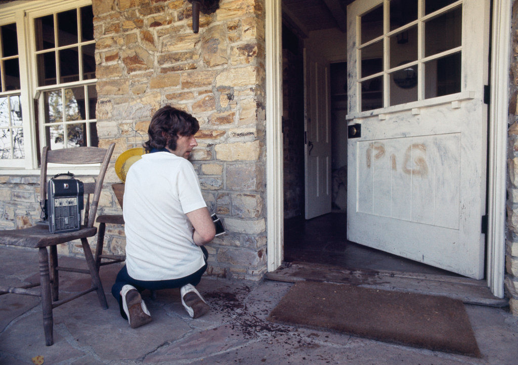 """Roman Polanski at home of the aftermath with the word """"PIG"""" in Sharon Tates blood on the door."""