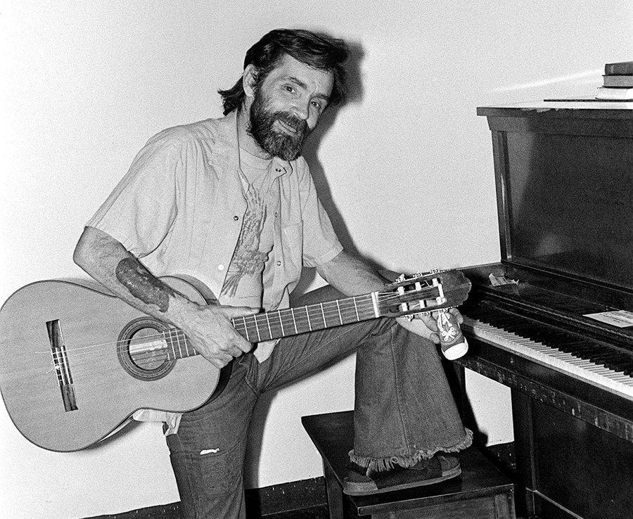 Charles Manson holding his guitar.
