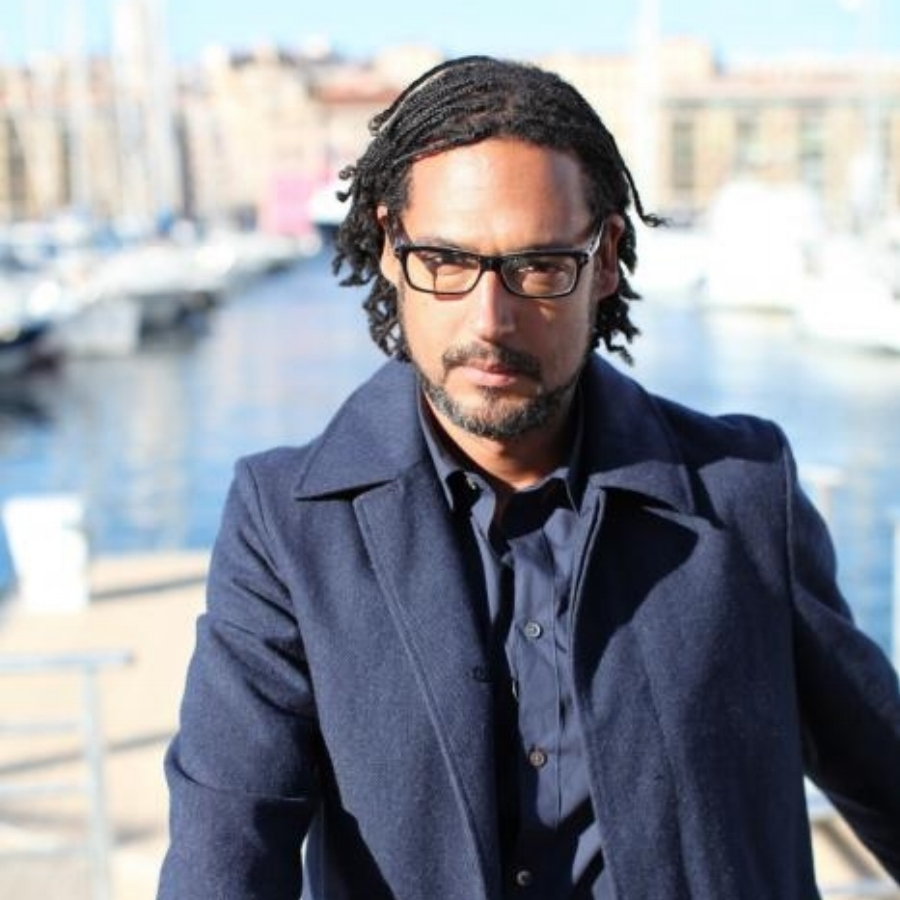 DAVID OLUSOGA  TV Presenter & Author  David Adetayo Olusoga is a British Nigerian popular historian, writer, broadcaster and filmmaker. His historical subjects have focused on military history, race and slavery.  Realising that black people were much less visible in the media and historically, including in the Ladybird Book of Roman Britain, Olusoga became a producer of history programmes after university, working from 2005 on programmes such as  Namibia Genocide and the Second Reich ,  The Lost Pictures of Eugene Smith  and  Abraham Lincoln: Saint or Sinner? .  His career in TV began in 2014 with The World's War: Forgotten Soldiers of Empire, about the Indian, African and Asian troops who fought in the First World War, followed by several other documentaries and appearances on BBC One television's The One Show.  In 2015 Olusoga co-presented  Civilisations , a sequel to Kenneth Clark's 1969 television documentary series  Civilisation , alongside the historians Mary Beard and Simon Schama.  Also a writer, Olusoga is the author of the 2016 book Black and British: A Forgotten History, which was awarded both the Longman-History Today Trustees Award 2017 and the PEN Hessell-Tiltman Prize 2017.