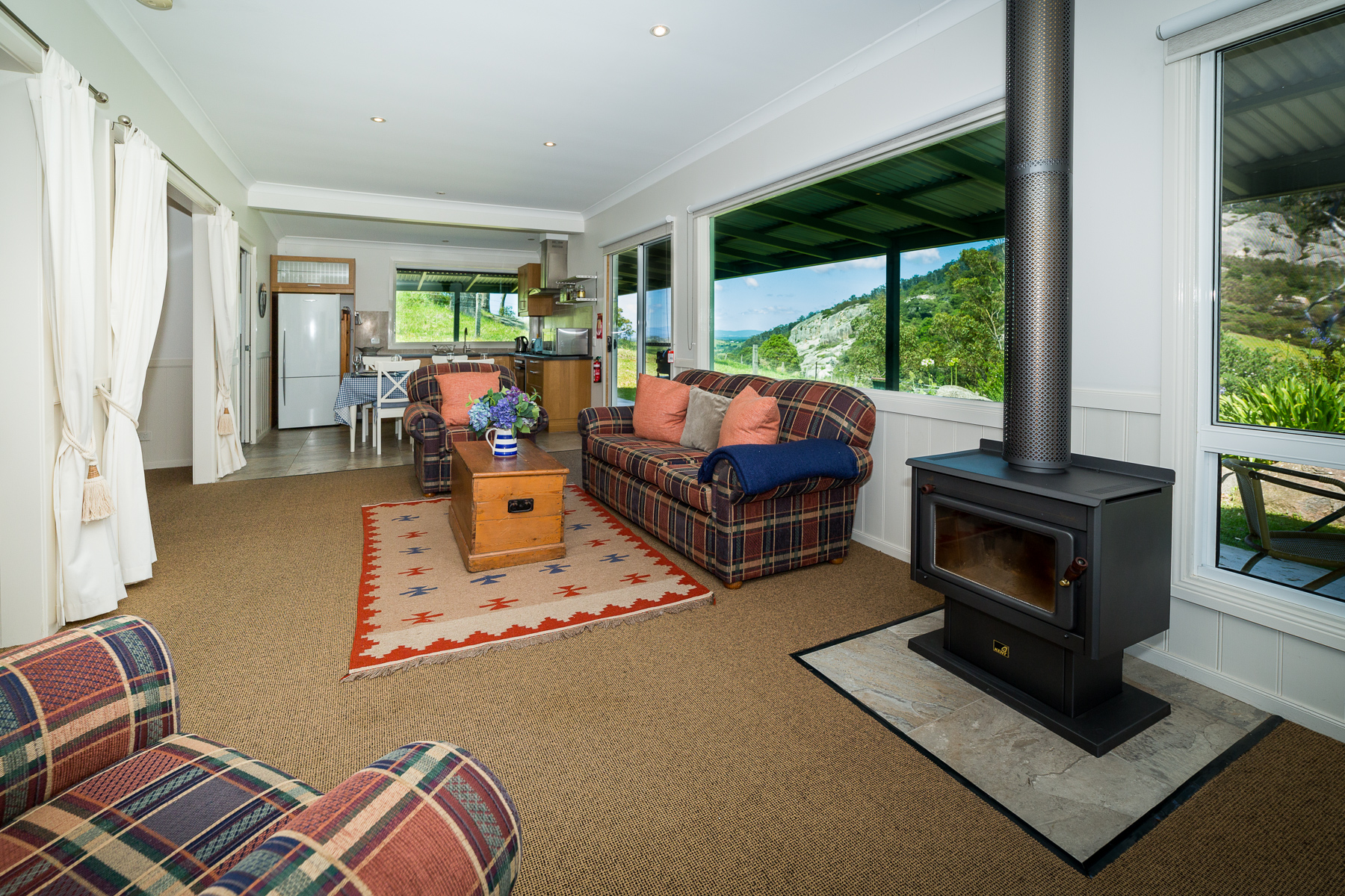 Sunny living room.. cosy wood combustion fire.. views from all rooms to nearby Gulaga