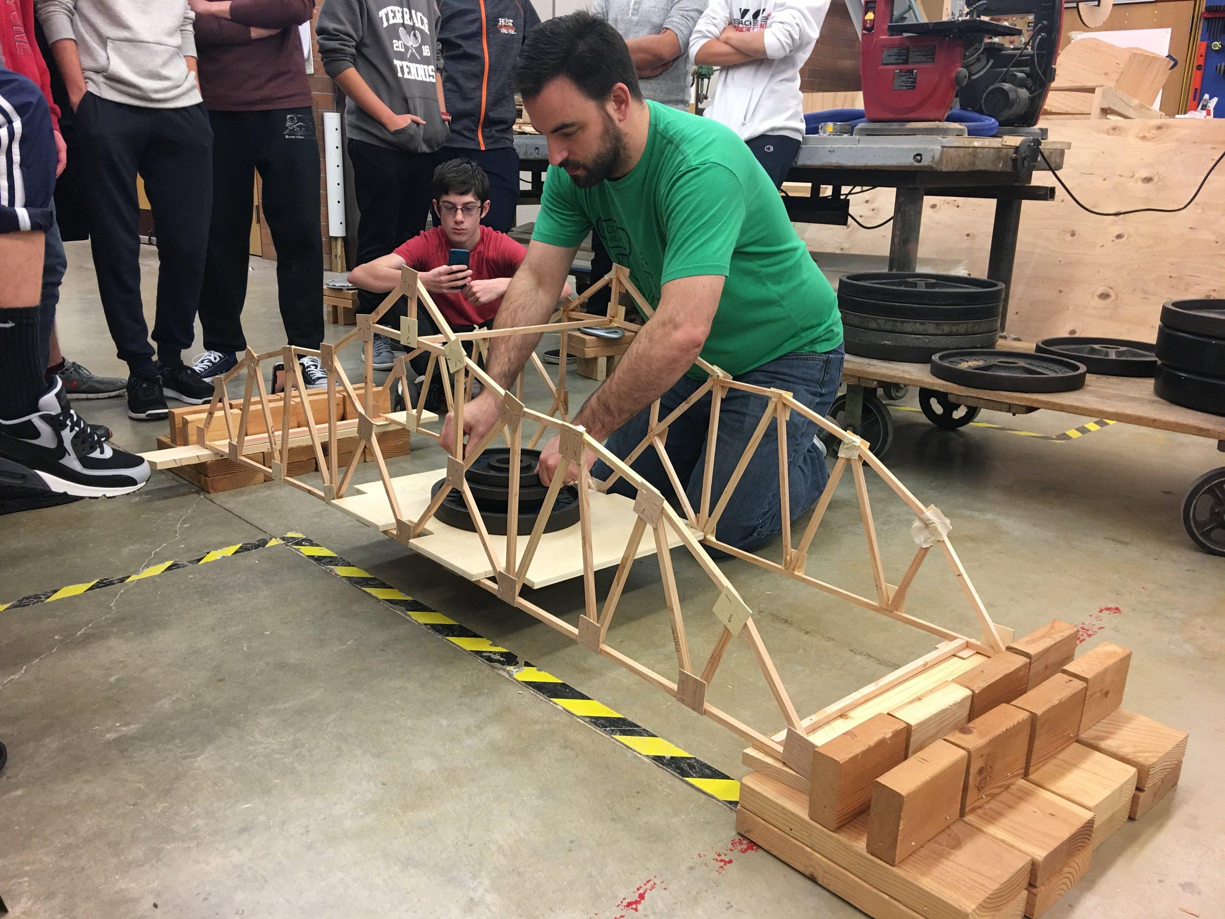 MTHS STEM teacher, Bryan Smelcer, tests a bridge.