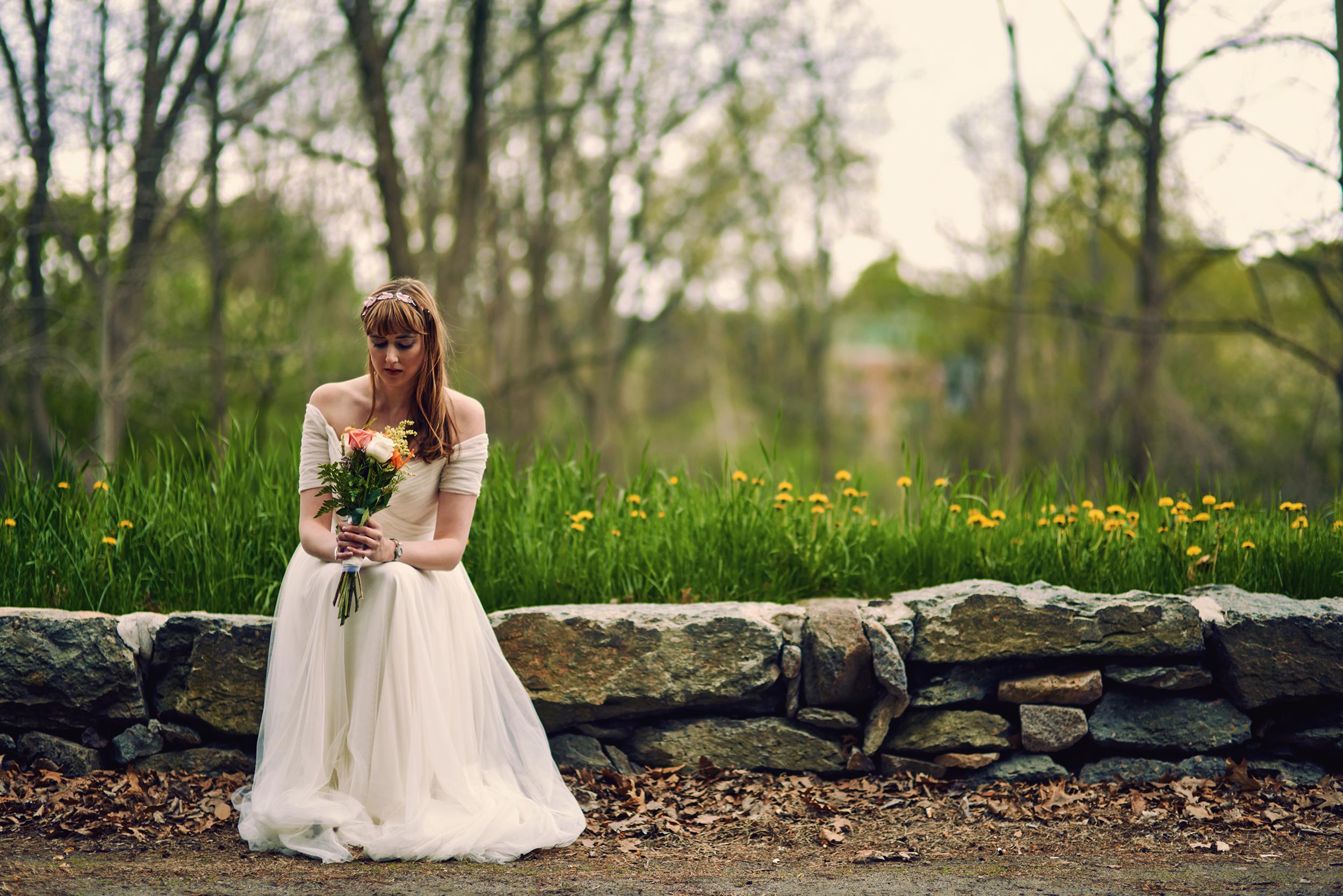 bride-on-stone-wall-in-garden.jpg