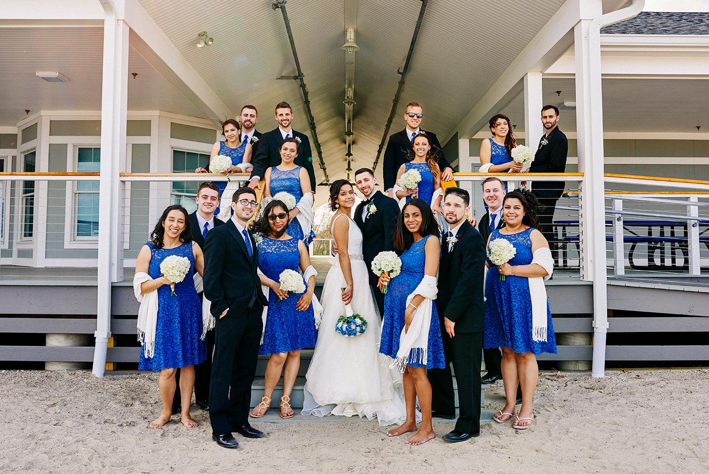 Wedding party photos at Fairfield Beach in Fairfield, CT. Bride and groom at the beach, bridal New England beach portraits, and wedding party fun photos at the beach.