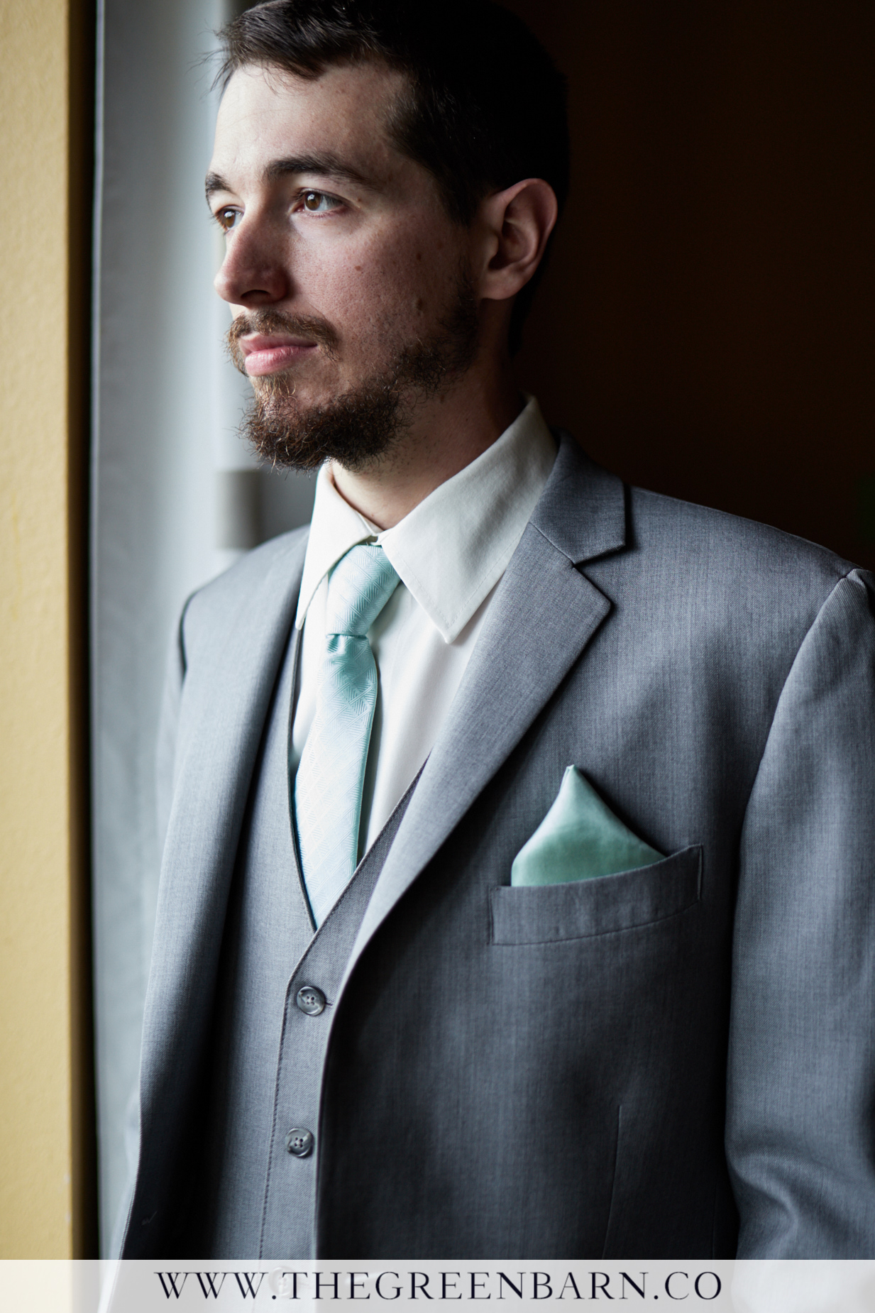 Groom Looking out the Window in a Hotel Room on his Wedding Day