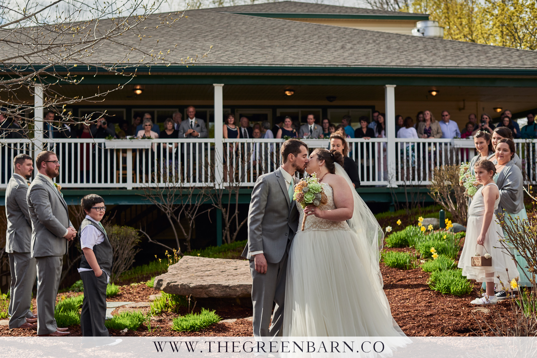 Bride and Groom First Kiss with All Guests Behind the Couple Photo at a Spring Garden Wedding in Vermont