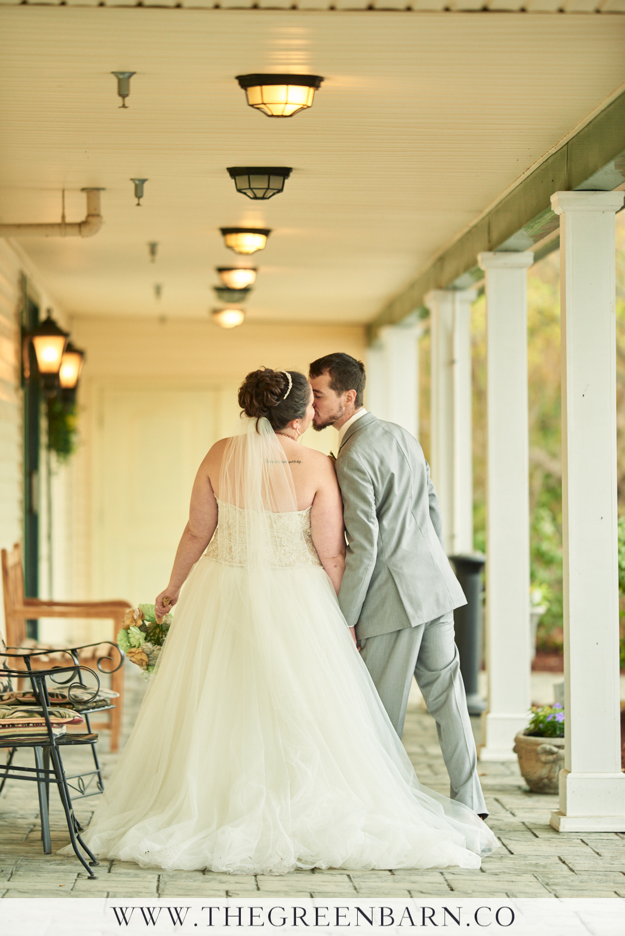 Bride and Groom Kissing on the Front Patio at Catamount Country Club in Northern Vermont