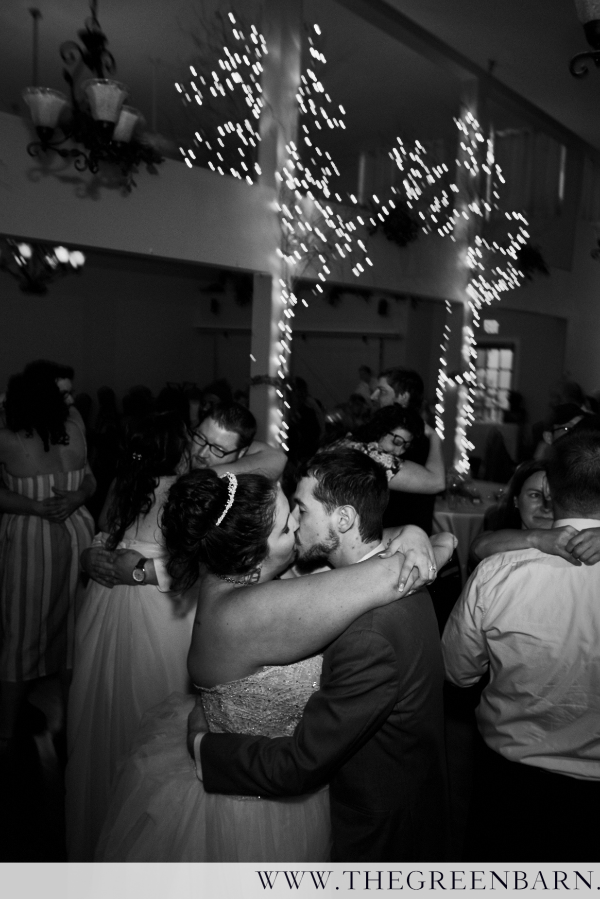Bride and Groom Dance Black and White Photo Kissing on Dance Floor Surrounded by Guests