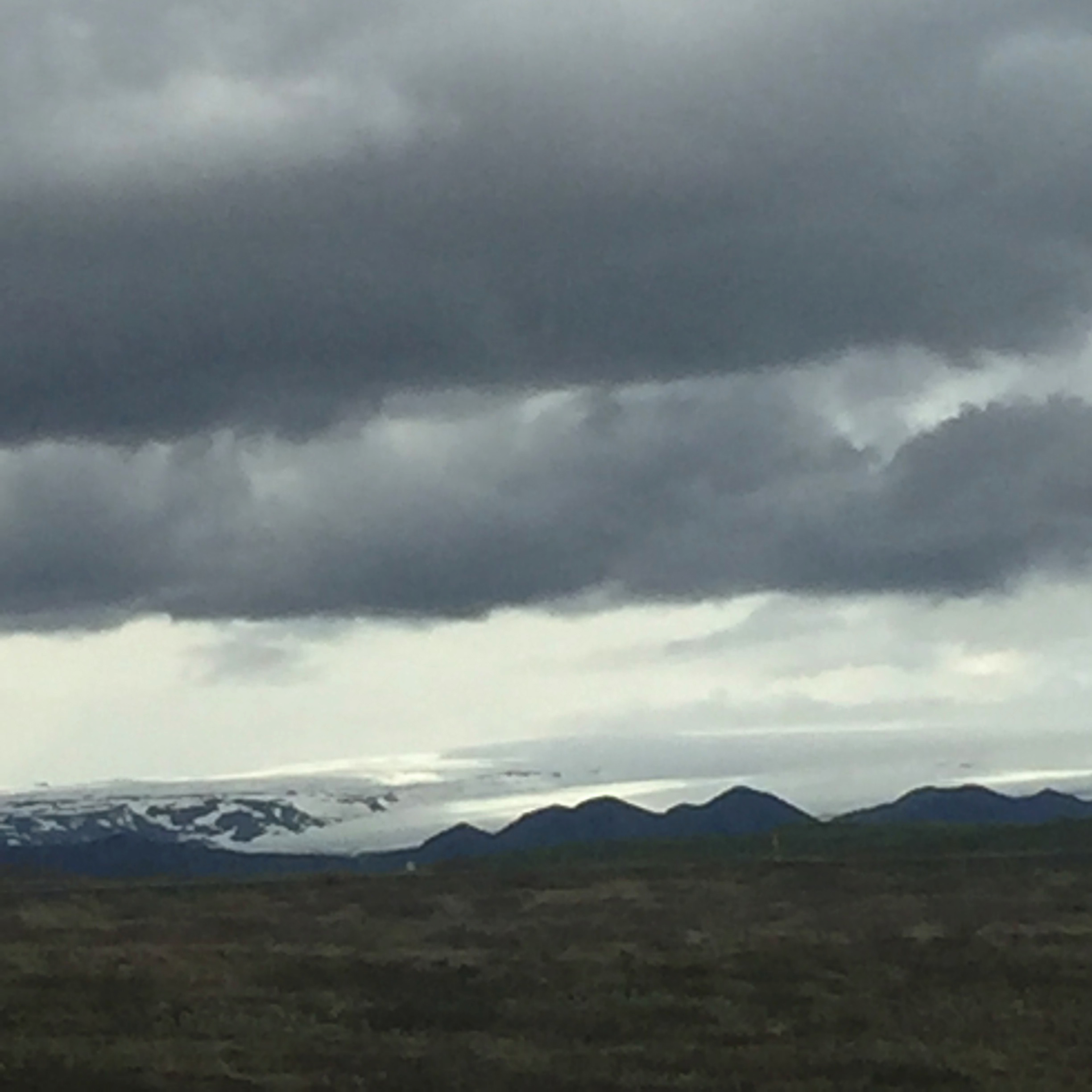 The glacier is visible merging into cloud. It could be Vatnajökul, the largest glacier in Europe.
