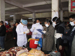On January 14, 2014, during an H7N9 avian flu investigation, China FETP residents collect environmental samples in a poultry market in Dongguan, Guangdong, China. Submitted by Shuqing Zhao – China. Source:  CDC Global Flickr.